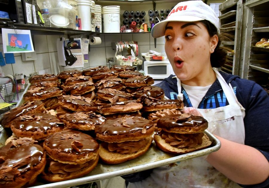 Francesca Ortiz carries a tray of Chocolate Lover's Dream paczkis at Central Continental Bakery in Mount Prospect.