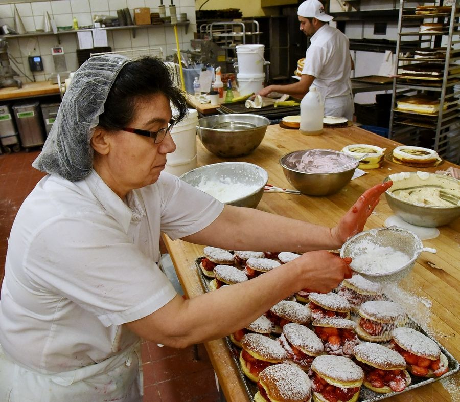 Connie Trakas sugars a tray of strawberry paczkis at Central Continental Bakery in Mount Prospect.