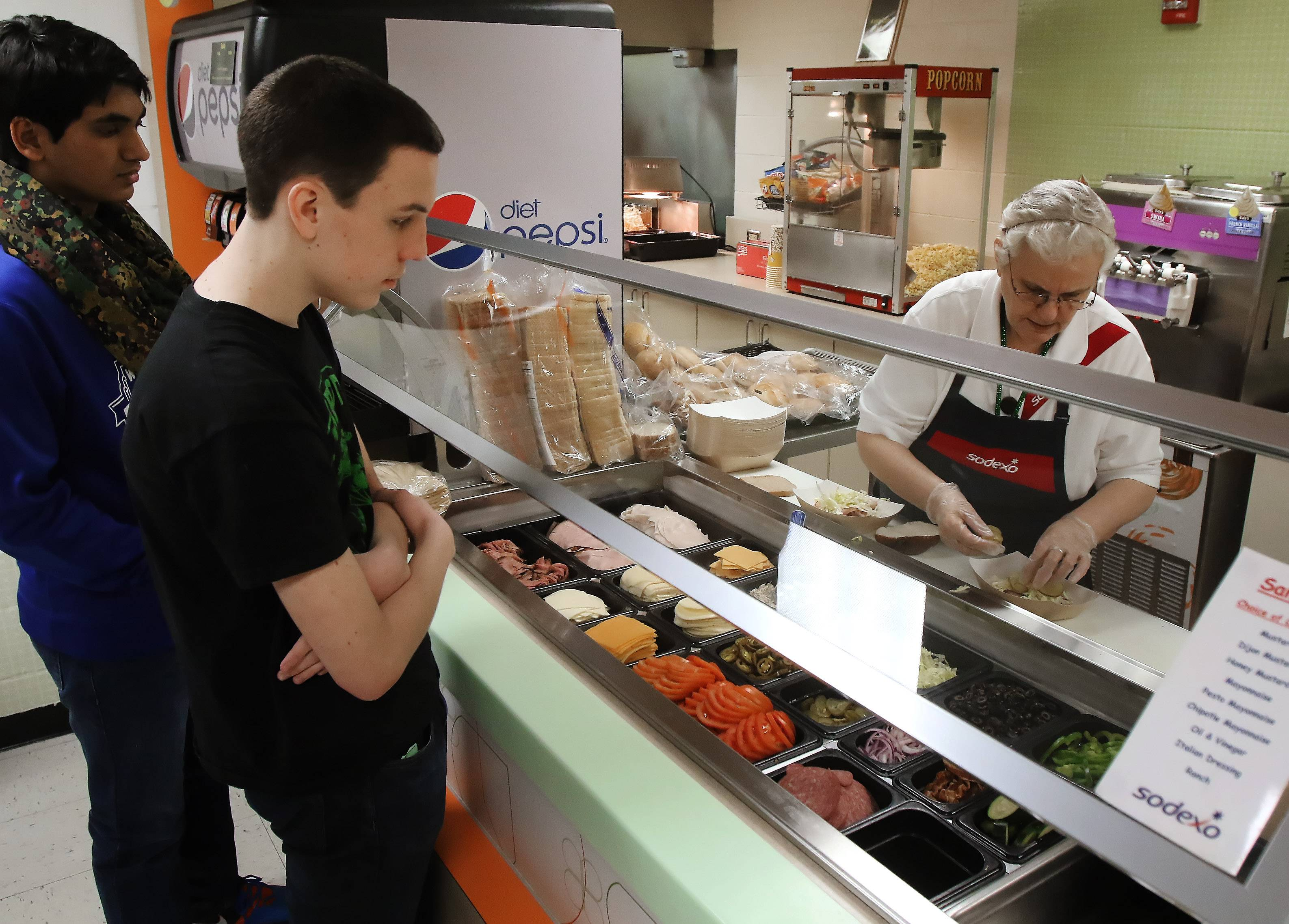 Stevenson High School junior Edward Kosinsky watches his sandwich made by Sodexo employee Kaliopi Gjermani at the Lincolnshire school Tuesday. Stevenson will offer healthier lunch options next year launched by Sodexo called Mindful menu.