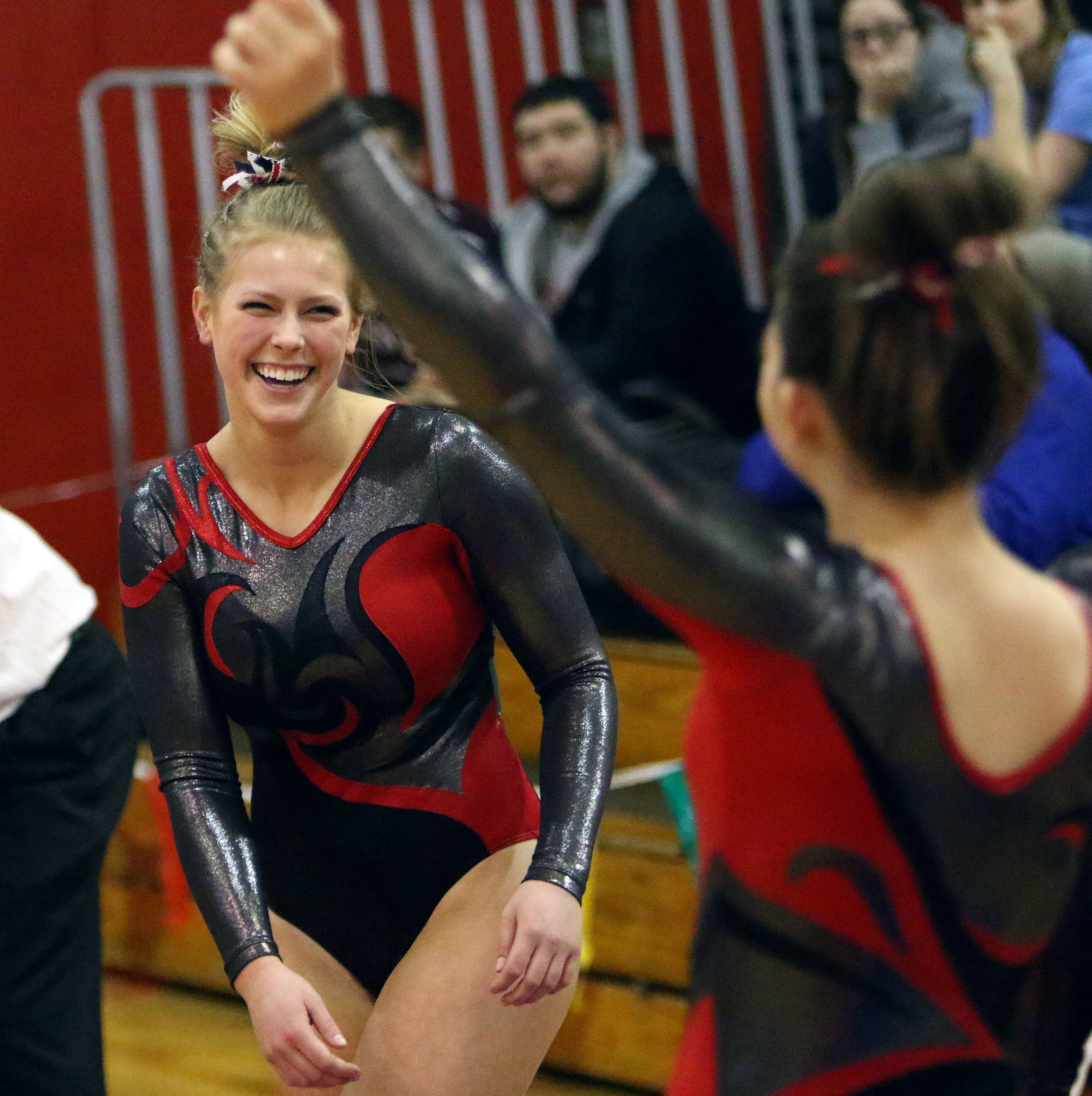 Mundelein's Meagan Kehr, left, celebrates after her vault during Tuesday's girls gymnastics sectional meet at Mundelein.