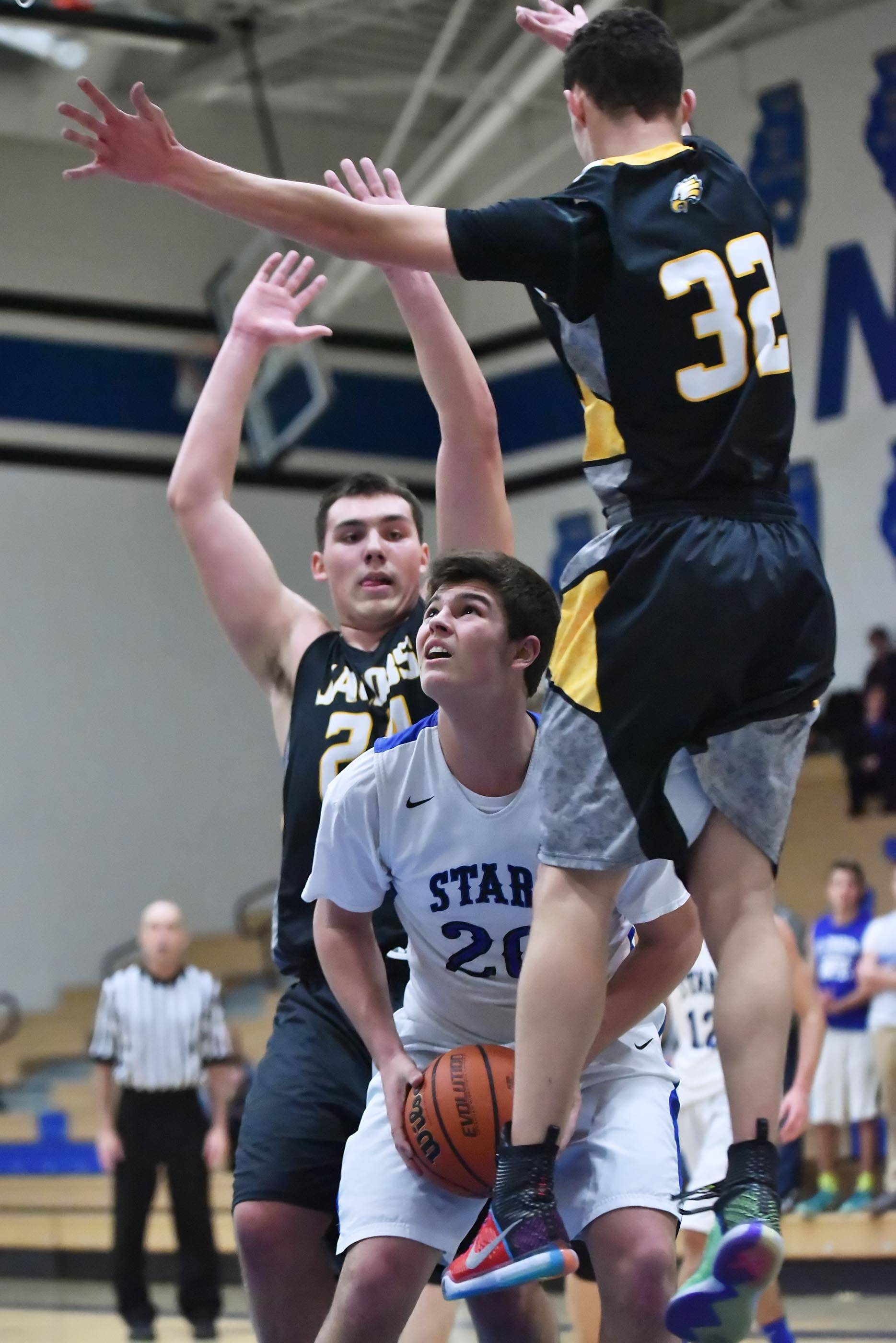 St. Charles North's Kyle King gets Jacobs' Nikolas Balkcom and Cameron Krutwig, left, to jump on his pump fake Tuesday in St. Charles.