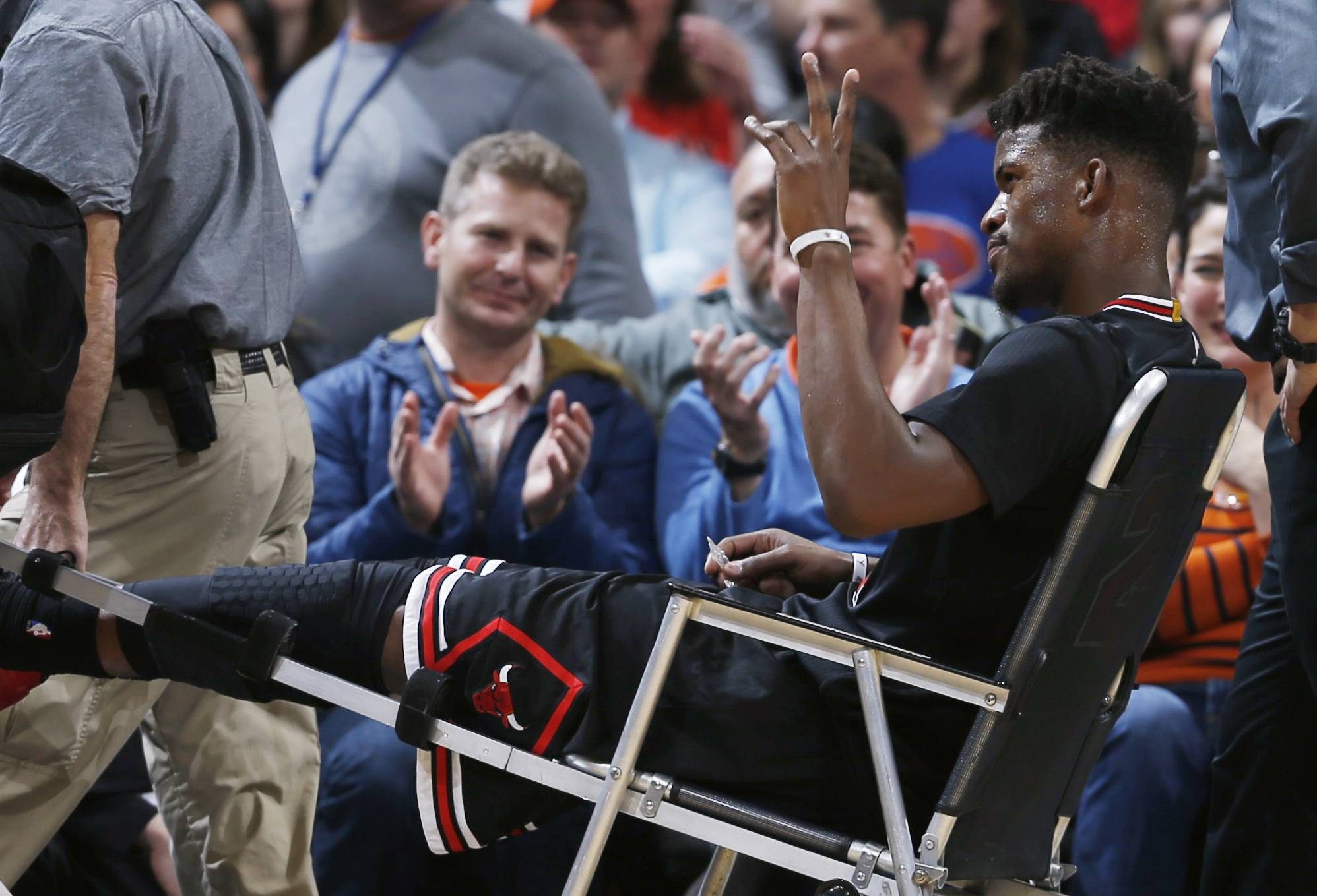 Chicago Bulls guard Jimmy Butler waves to fans Friday as he is taken off the court after being injured late in the first half against the Denver Nuggets. The knee injury will keep Butler out of the all-star game.