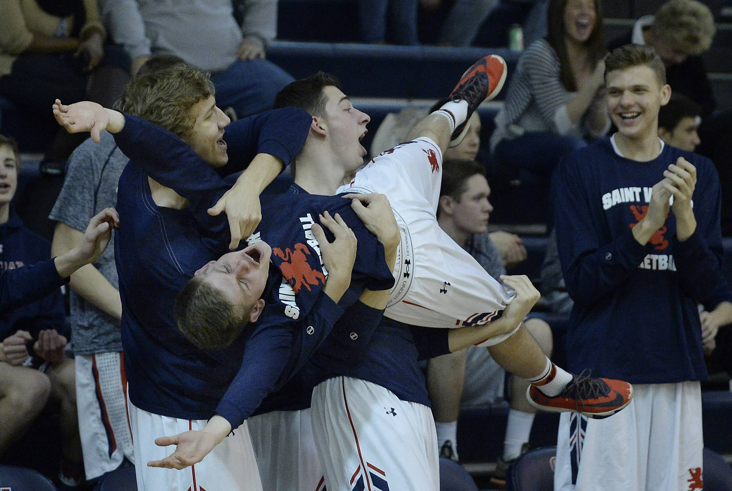 St. Viator's Trevor Koos and his teammates celebrate a point and the eventual win over Joliet Catholic Academy in boys varsity basketball at St. Viator on Thursday.