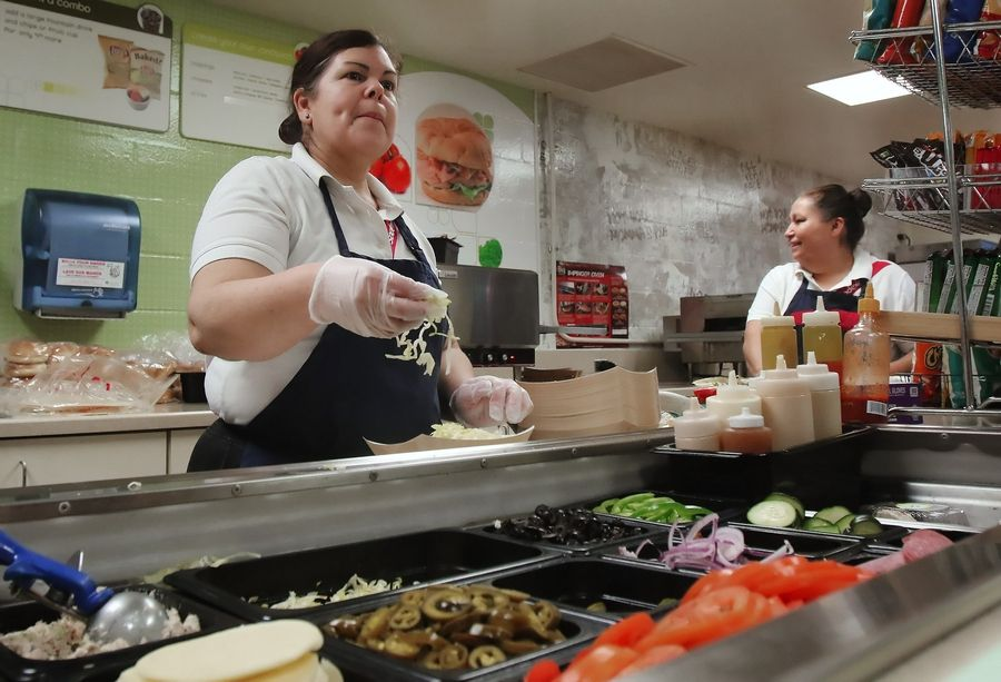 Sodexo employee Olga Rodriguez makes a sandwich for a Stevenson High School student Tuesday. The Lincolnshire school will offer healthier lunch options next year launched by Sodexo called Mindful menu.