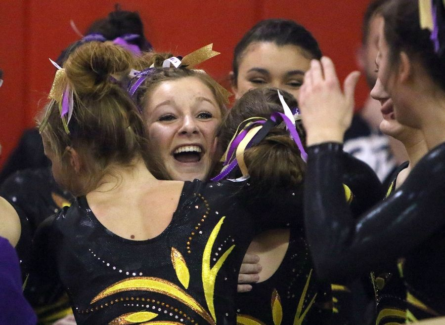 Carmel's Madison Graff celebrates with teammates after her vault during Tuesday's girls gymnastics sectional meet at Mundelein.
