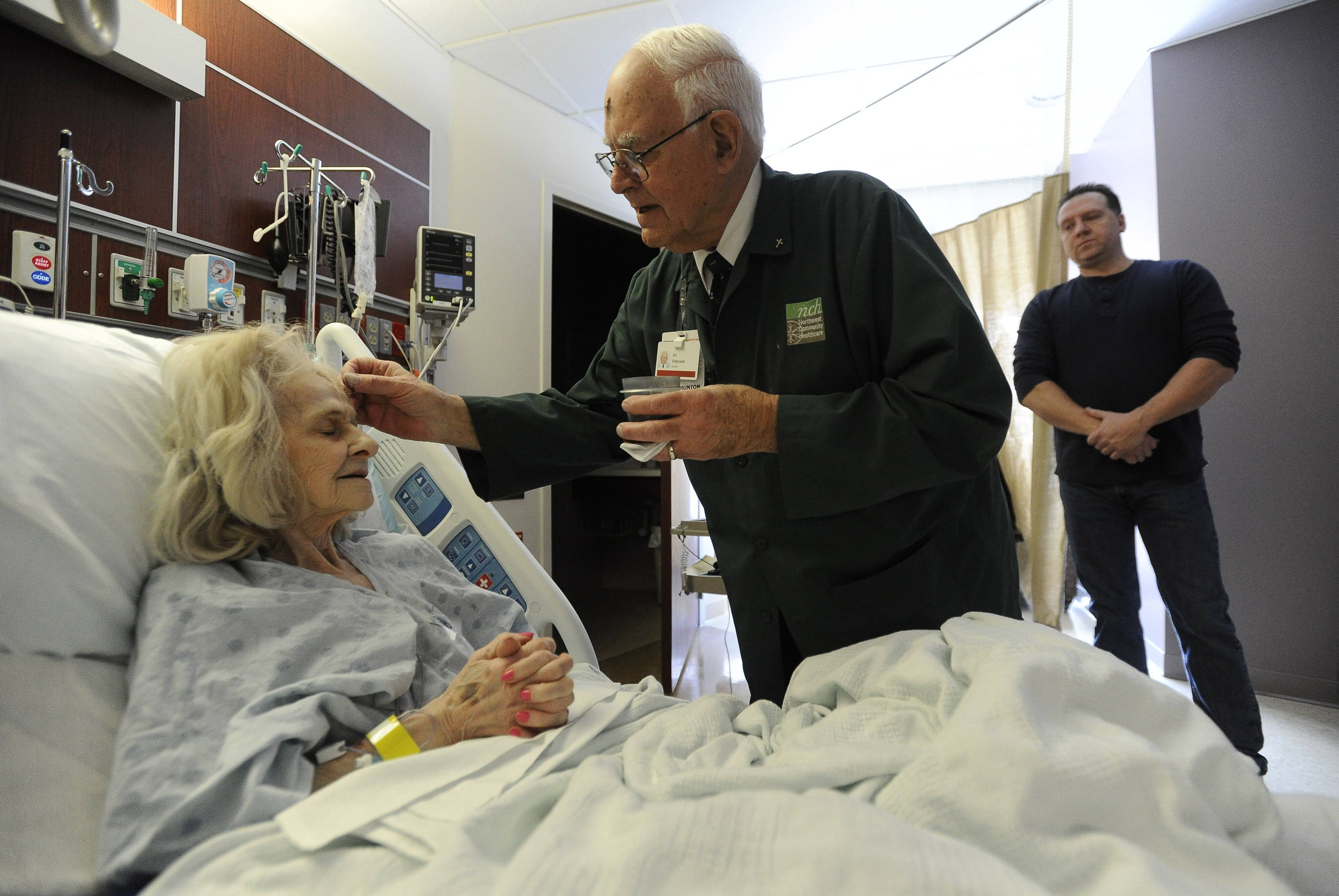 Eucharistic minister Jim Walkowiak from St. Raymond's Church of Mt. Prospect places ashes on the forehead of Northwest Community Hospital patient Mildred Leon of Arlington Heights as her nephew Don Ruzecki of Wheeling looks on.