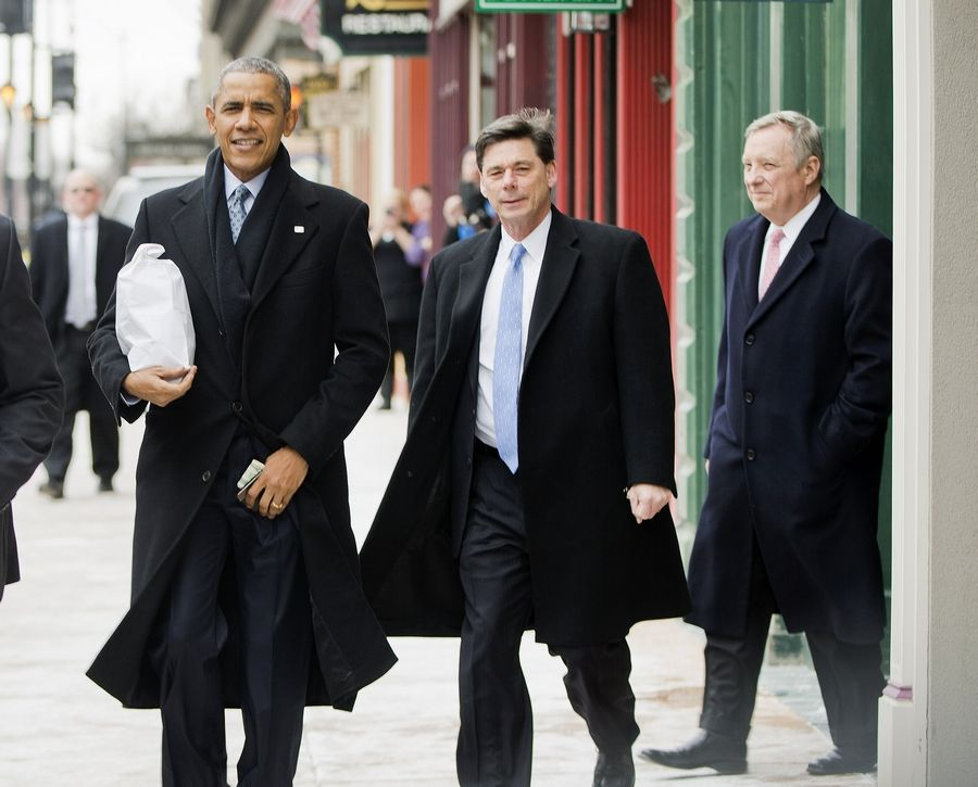 President Barack Obama, followed by a Secret Service agent, center, and Senate Minority Whip Richard Durbin of Springfield, puts away his money clip after picking up his order during an unscheduled stop at the Feed Store restaurant Wednesday in Springfield.