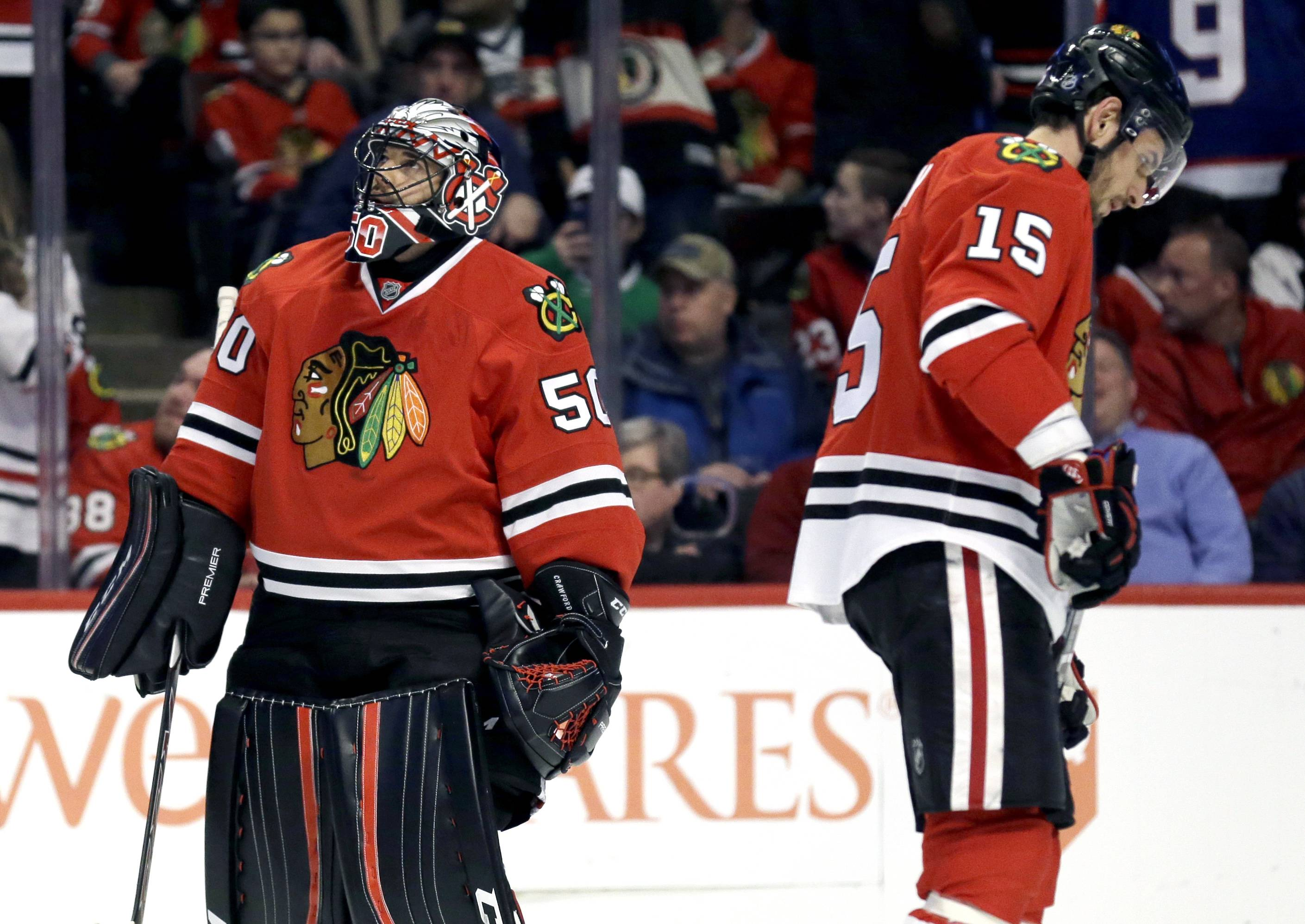 Chicago Blackhawks goalie Corey Crawford, left, looks at the scoreboard and center Artem Anisimov can't bear to look after the Stars scored four times in Thursday's first period.