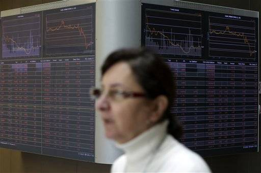 An employee passes next to an index board at the reception hall of the Stock Exchange in Athens, Thursday, Feb. 11, 2016. Banks, particularly in Europe, have come under pressure over recent days as investors fret about their ability to cope with a bigger than expected global slowdown at a time when many still have sizeable bad loans on their books. Greece is expected to slip back into a mild recession in 2016, while the global sell-off in financial markets saw the value of shares on the Athens Stock Exchange sink to their worst level since 1989. (AP Photo/Thanassis Stavrakis)