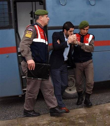 Prison guards escort Asem Alfrhad before his trial in Aegean resort of Bodrum, Turkey, Thursday Feb. 11, 2016. Two alleged people-smugglers are on trial accused of causing the death of 3-year-old Syrian migrant boy Aylan Kurdi and four other people. The image of the boy - his lifeless body lying face down on a beach in Bodrum - galvanized world attention on the refugee crisis, graphically illustrating the magnitude of the suffering and the treacherous journeys the migrants risk. (DHA via AP ) TURKEY OUT