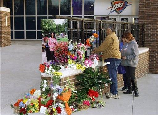 Thunder fans drop off flowers at a memorial for Ingrid Williams, the wife of Thunder assistant coach Monty Williams, who died Wednesday as the result of a car accident Tuesday, before an NBA basketball game between the New Orleans Pelicans and the Oklahoma City Thunder in Oklahoma City, Thursday, Feb. 11, 2016. Ingrid Williams' photo is on display at left.(AP Photo/Sue Ogrocki)