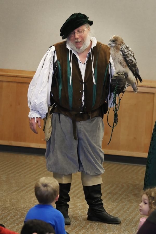 """Royal Falconer"" Mark Booth holds a red-tailed hawk as he showcases his birds of prey Monday at the Ela Area Public Library in Lake Zurich."