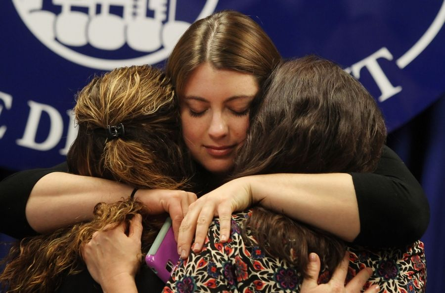 Executive Director Chelsea Laliberte of Live4Lali, center, hugs Tina Franco of Mundelein, left, and Terri Bartlett of McHenry after Lake County State's Attorney Mike Nerheim announced a naloxone training police program in 2014. All three women have lost loved ones to overdoses.