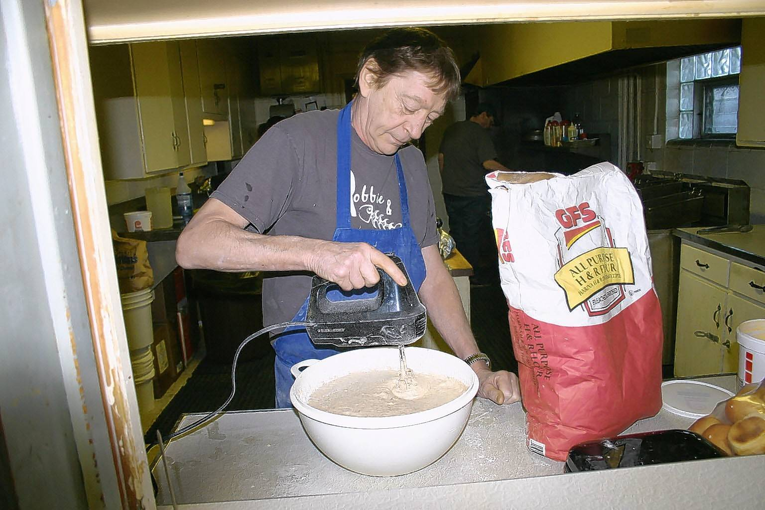 At the Veterans of Foreign Wars post in West Dundee, cook Robbie Robinson mixes secret ingredients into a bowl full of batter that will coat the cod he serves to 100 patrons. The post serves a fish fry on Friday nights, January through May.