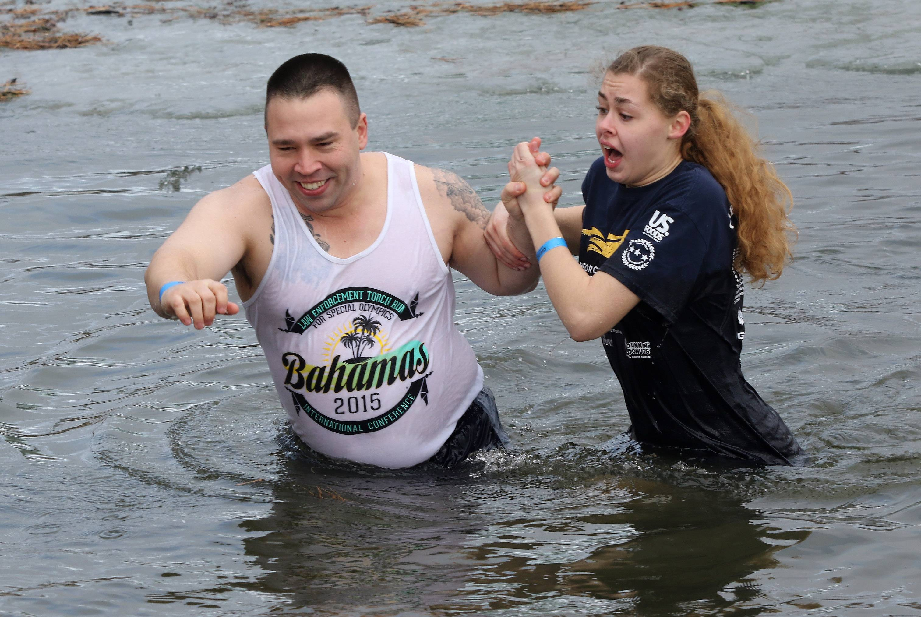 Carpentersville police officer Joe Pilarski and Special Olympics athlete Bree Bogucki walk in the frigid water during the annual Palatine Polar Plunge on Sunday at Twin Lakes Recreation Area in Palatine. The event is presented by the Law Enforcement Torch Run and GEICO to support Special Olympics athletes.
