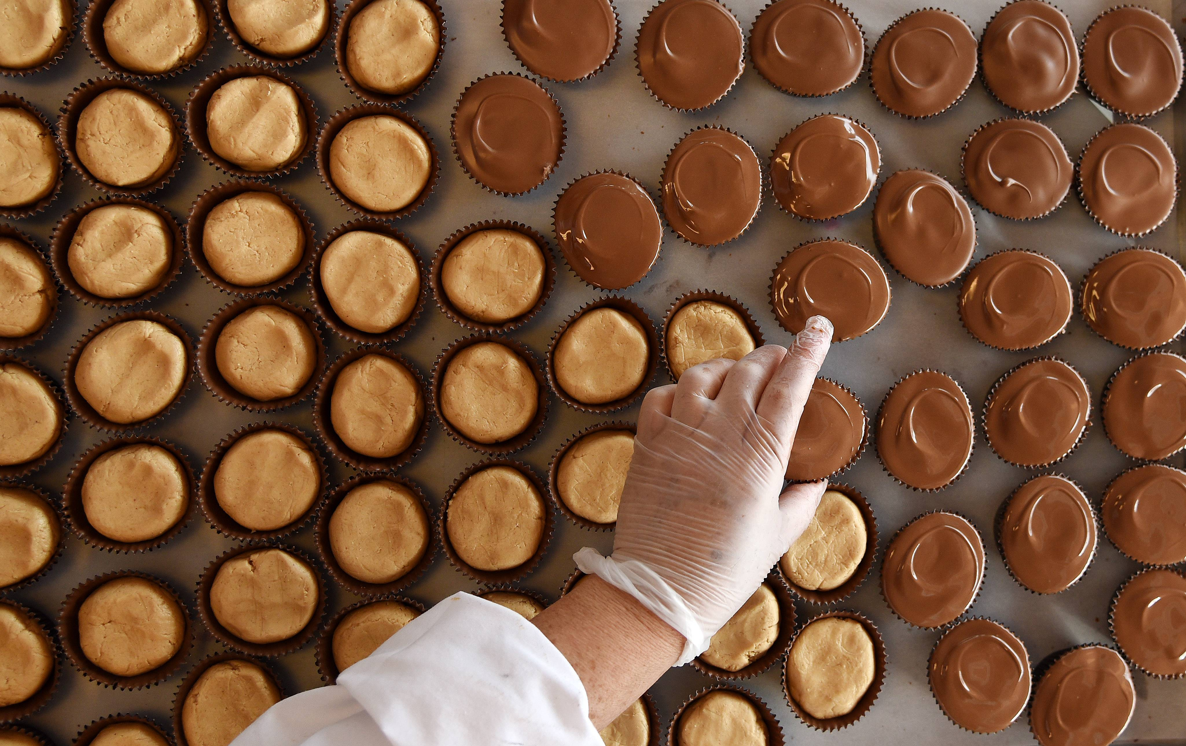 Juana Galvan makes a fresh tray of peanut butter cups at Graham's Fine Chocolates & Ice Cream in Geneva Tuesday. She's worked there for 14 years.