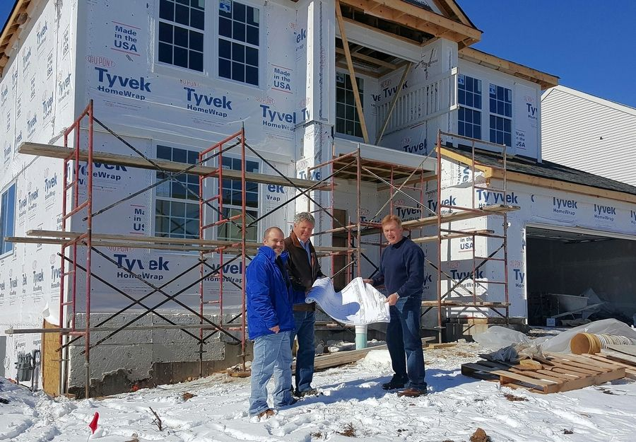 Bill Schey, right, owner of Insignia Kitchen & Bath, discusses grading and landscape plans with Fabio Avona and Bill Noyes outside the Johnsburg house he's building for the Folds of Honor military charity. The services are being donated by Mac's Property Management.