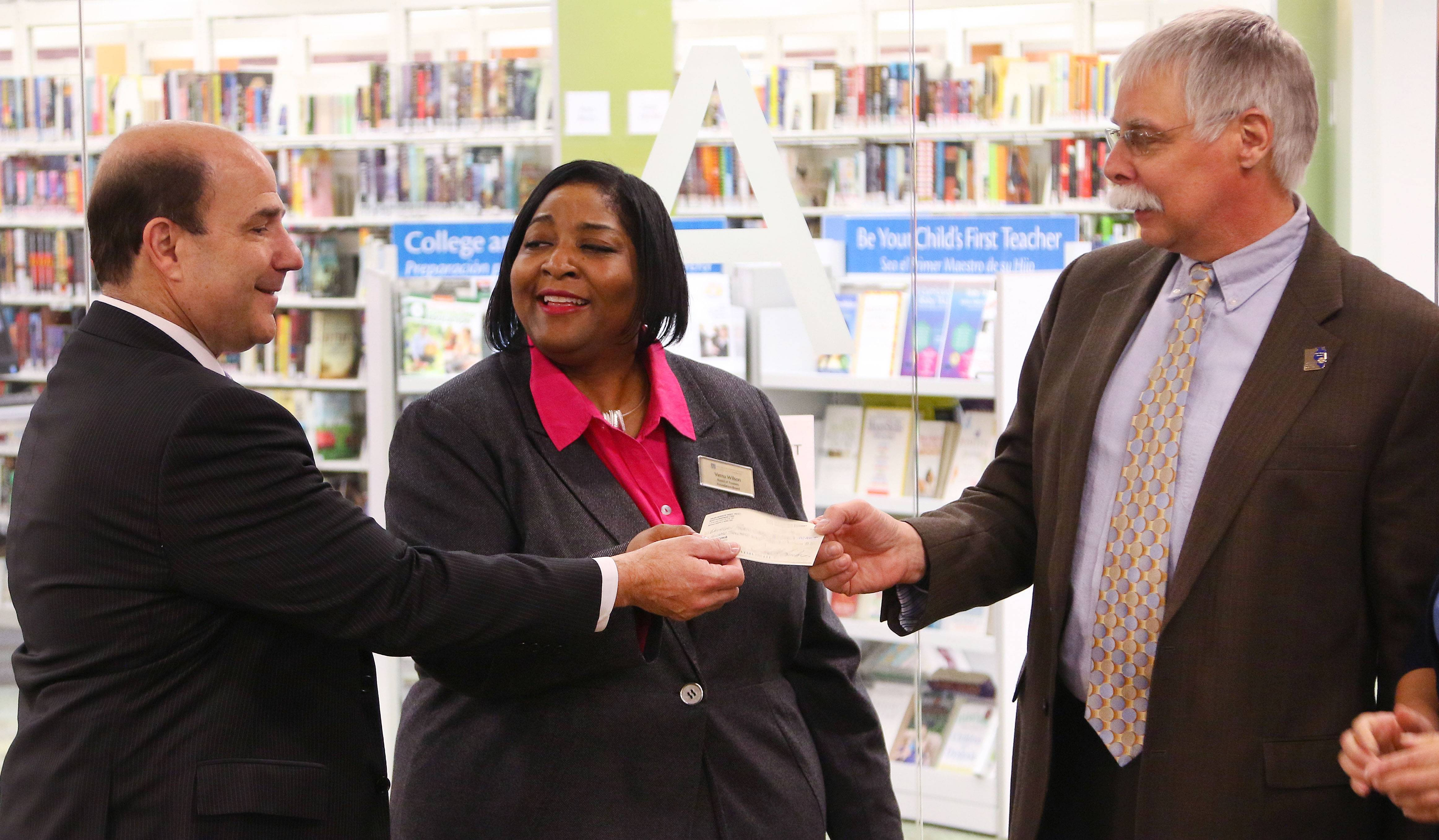 Attorney Scott B. Friedman, left, presents Verna Wilson, president of the Waukegan Public Library Foundation, and Richard Lee, right, executive director of the library, with a check for $100,000 from the estate of Helen N. Morrow, a Wilmette resident who died last fall. The money will be used for its literacy initiative, library officials said.