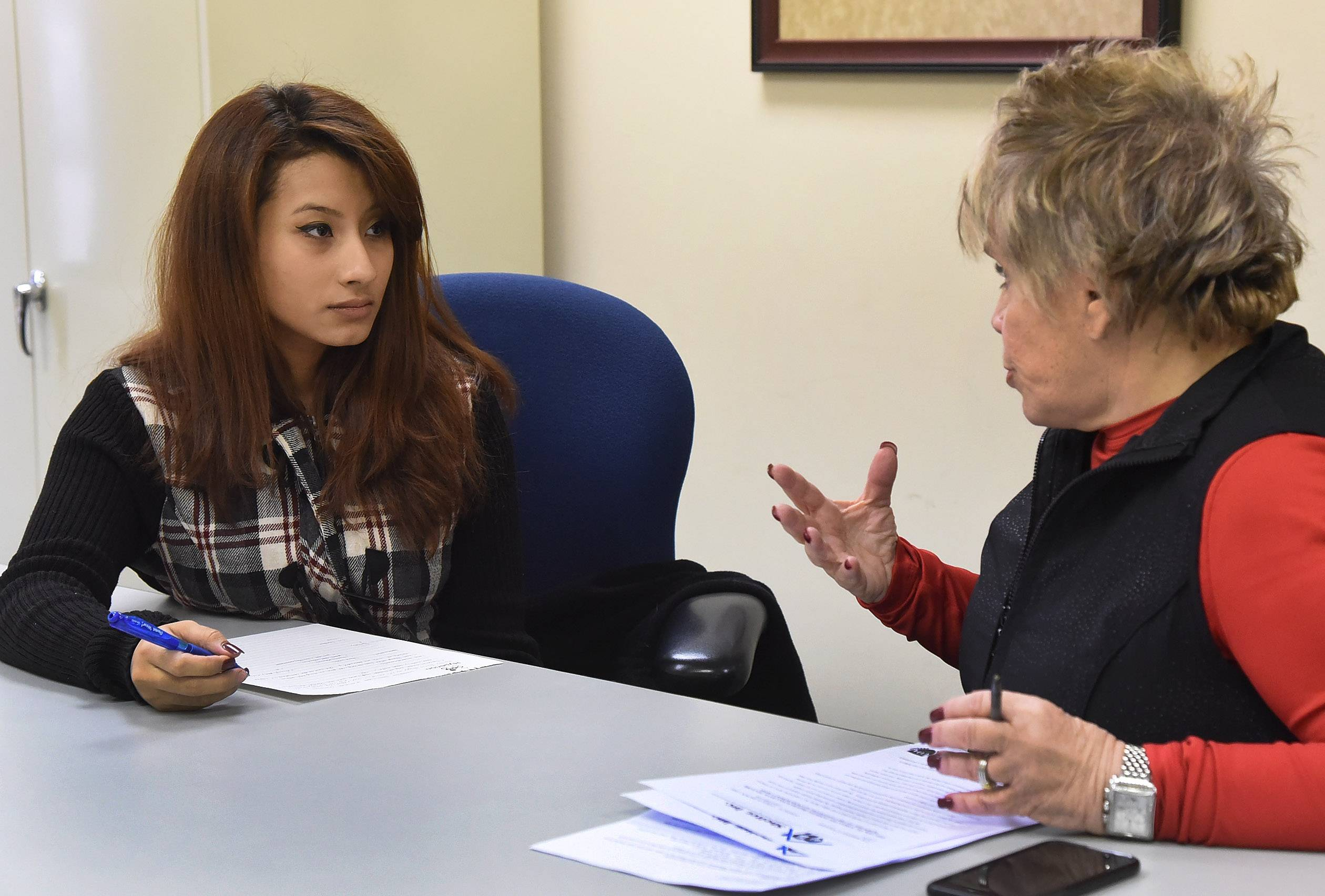 Gloria Jimenez, of Mount Prospect, left, talks with Carol Brown, Shelter Inc.'s director of development, at the Arlington Heights office.