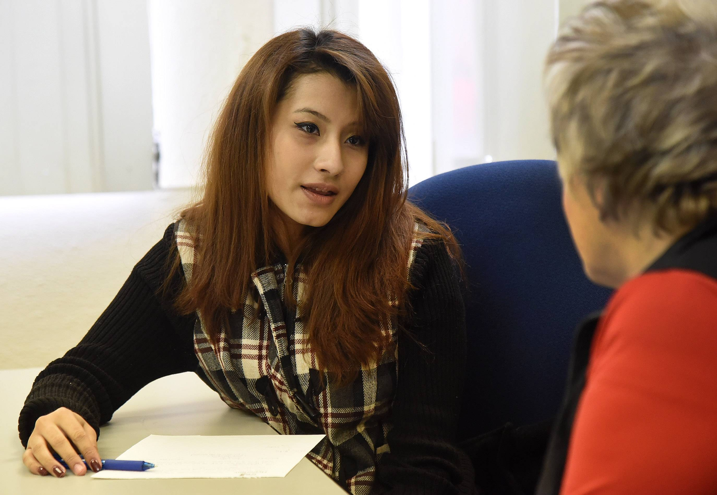 Gloria Jimenez of Mount Prospect, left, talks with Carol Brown, Shelter Inc.'s director of development, at the Arlington Heights office.