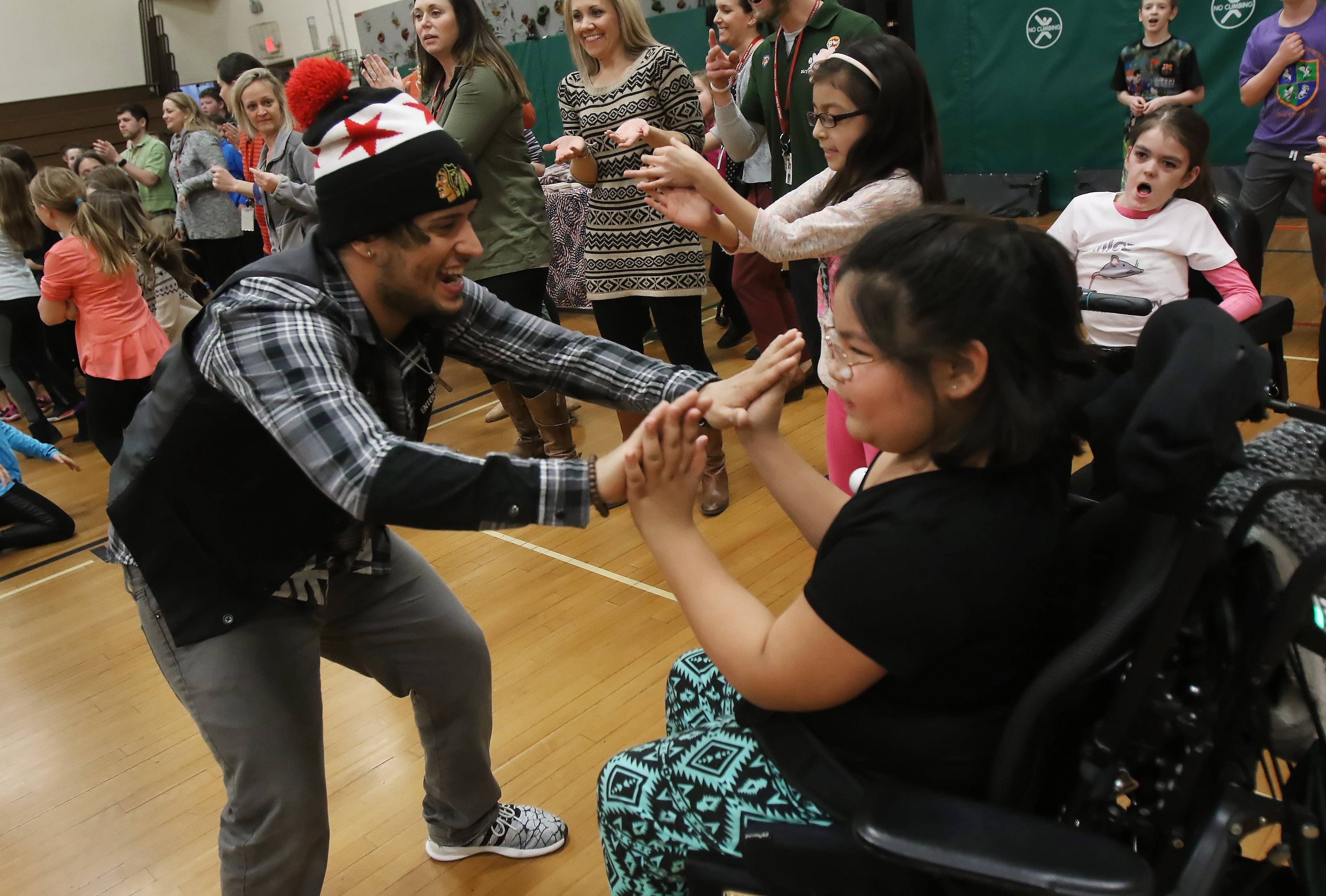 Pride (Raymond Masciopinto) dances with third grader Maura Nakanant during the Dr. Cool and Pride show Tuesday at Butterfield School in Libertyville. Dr. Cool and his crew interacted with students dancing and singing while teaching lessons of empowerment.