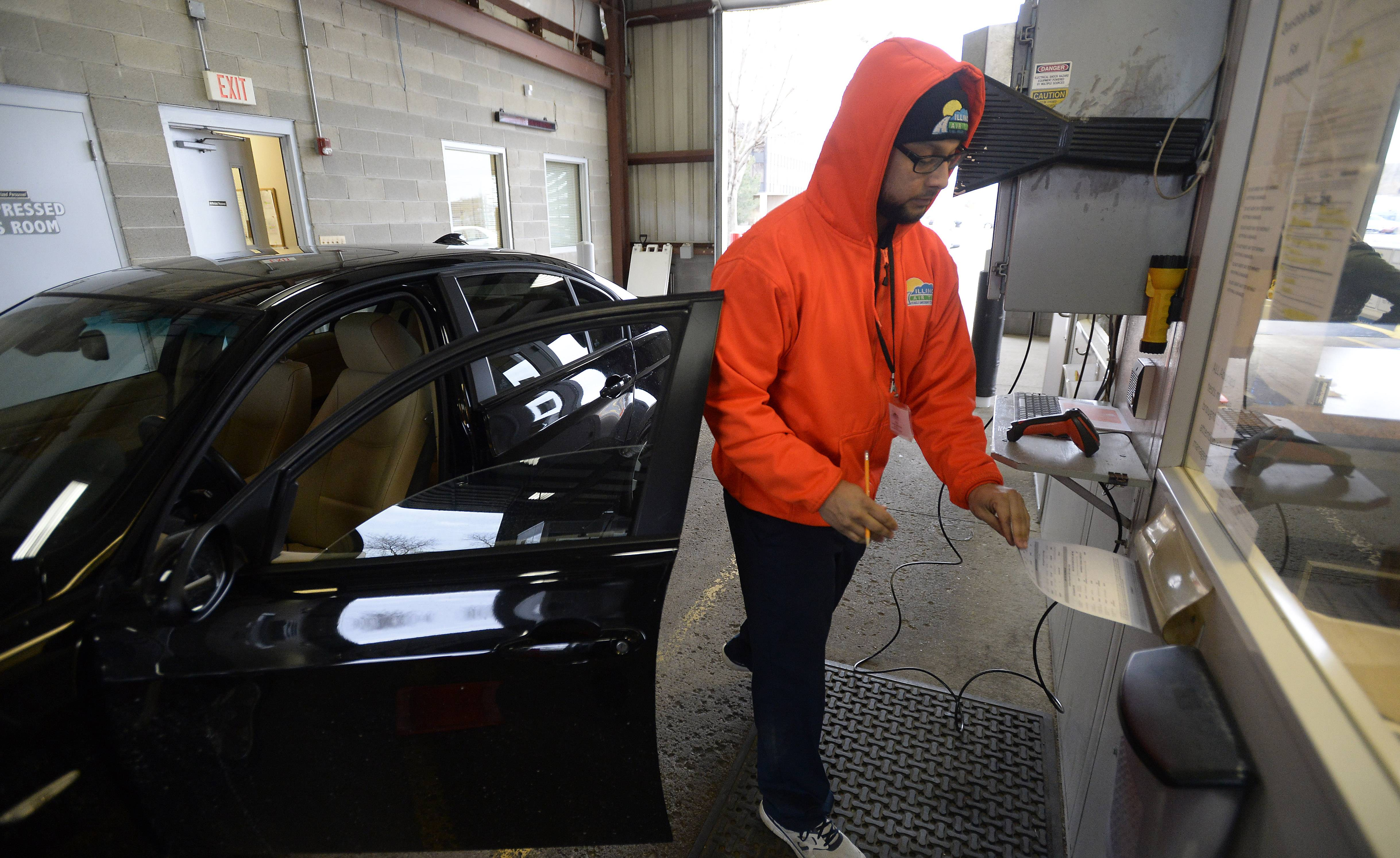 Vince Delmoral, an IEPA traveling customer service representative, attends to a driver who brought a car in for emissions testing Thursday at an Elk Grove Village facility.