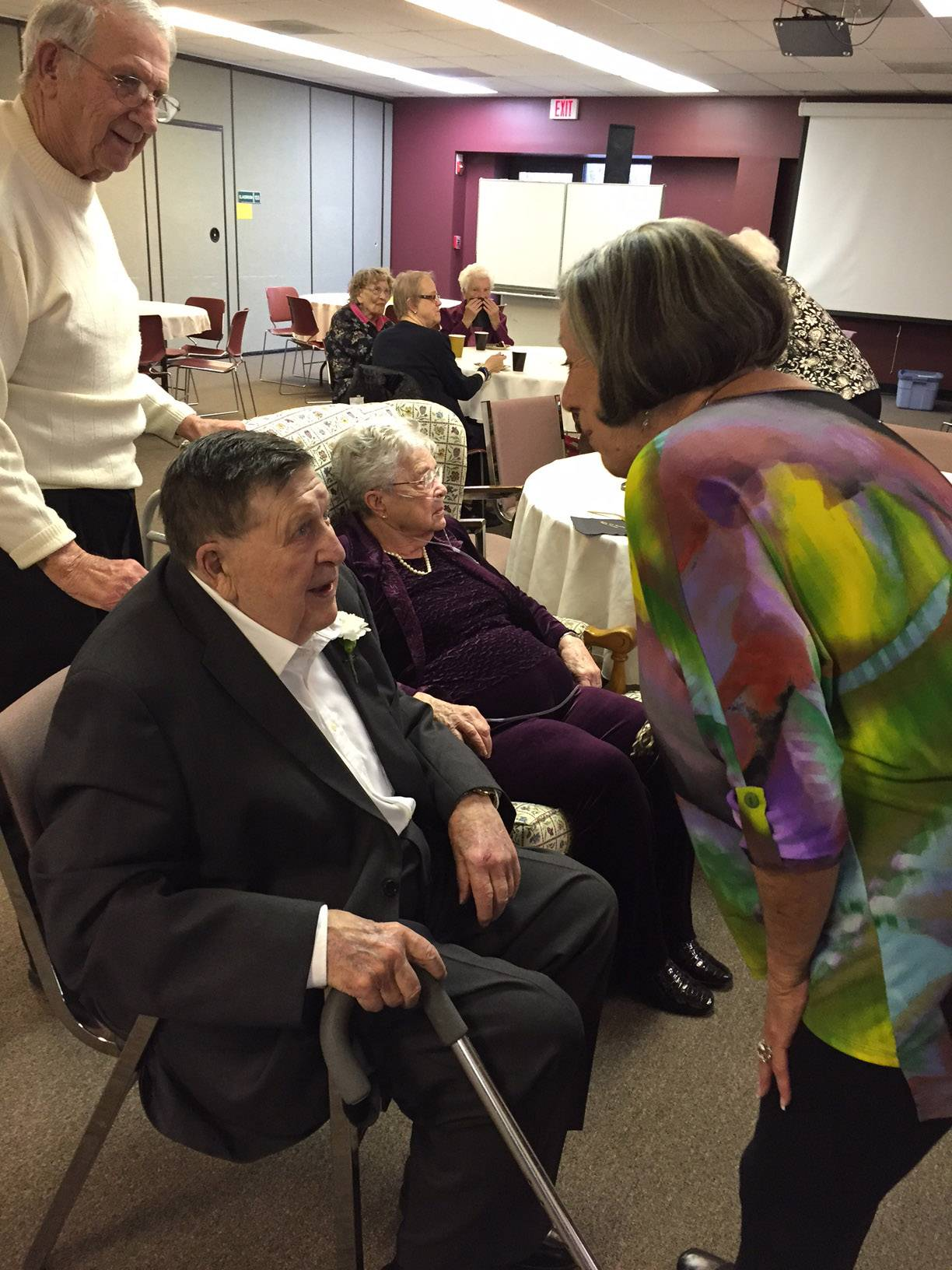 Melvin Peterson, seated, chats with visitors at his recent 95th birthday party at Bethlehem Lutheran Church in St. Charles. His wife, Ruth, is seated next to him.