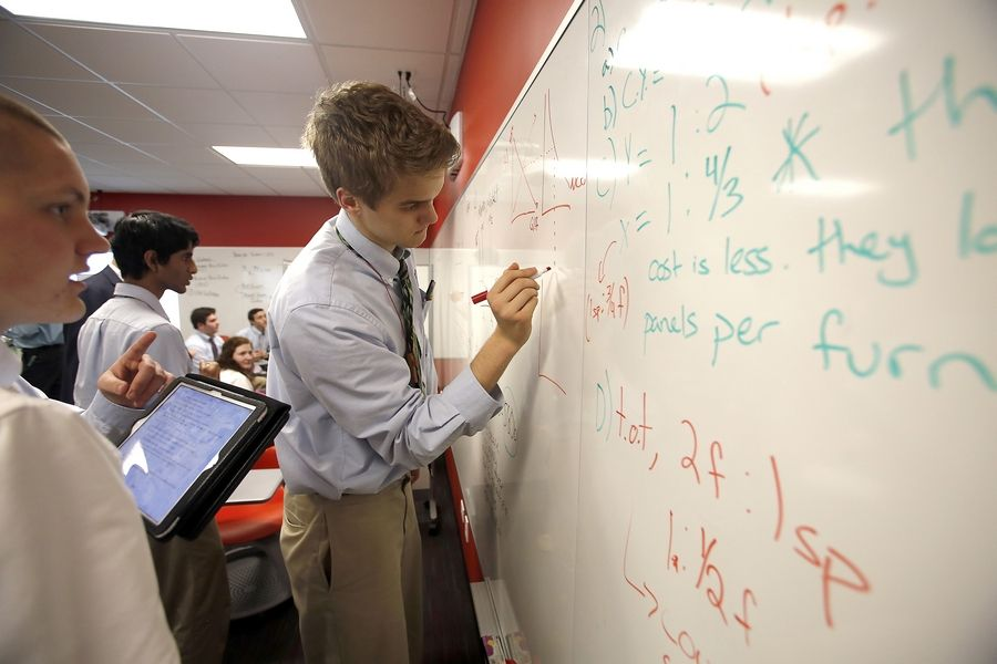 Christopher Yates works with his group to solve one of the problems in his advanced placement economics class at Benet Academy in the school's new Idea Studio.