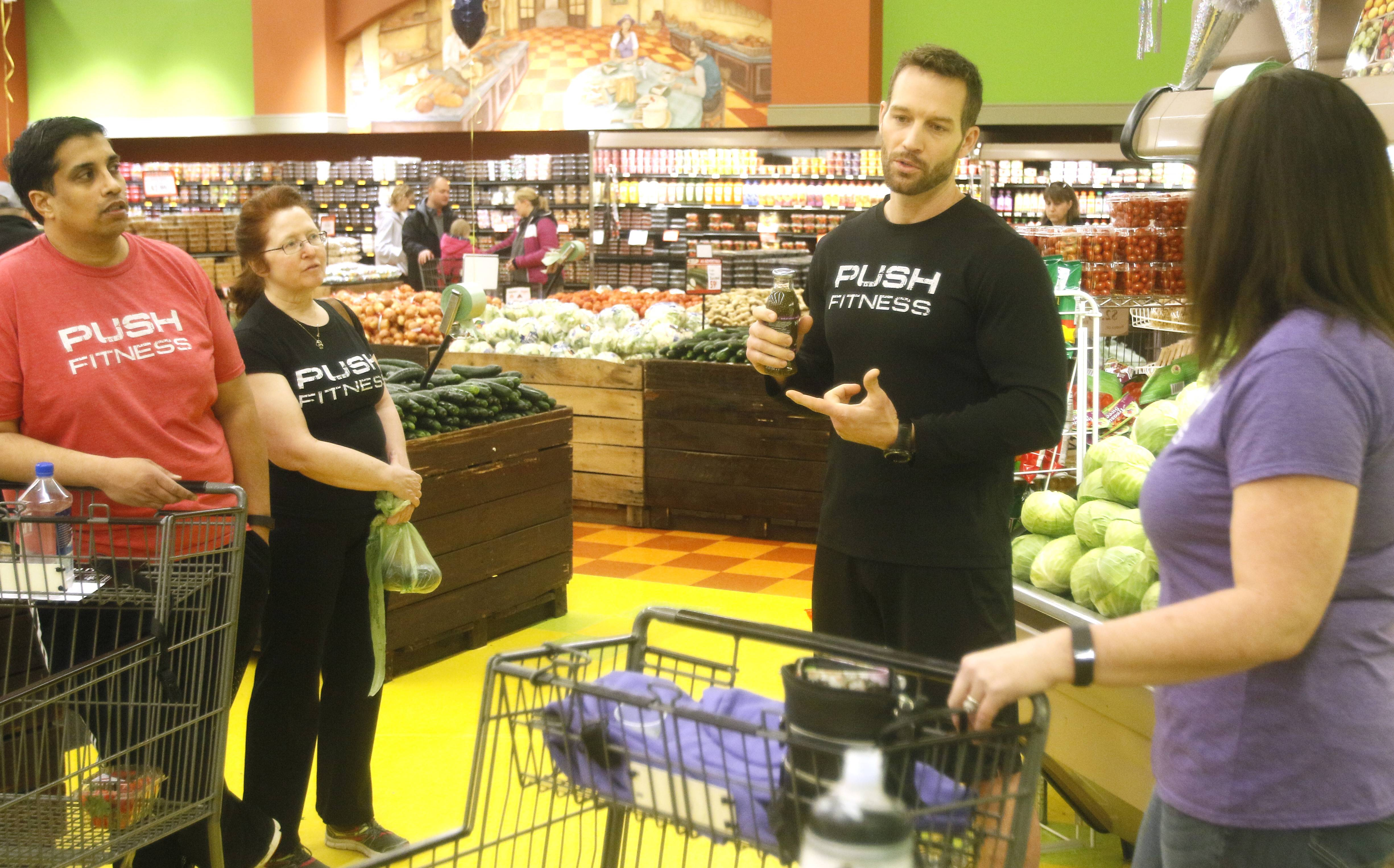 Push Fitness trainer Josh Steckler guides the Fittest Loser contestants toward powerhouse produce items such as spinach, kale, broccoli, avocados and berries at Valli Produce in Glendale Heights.