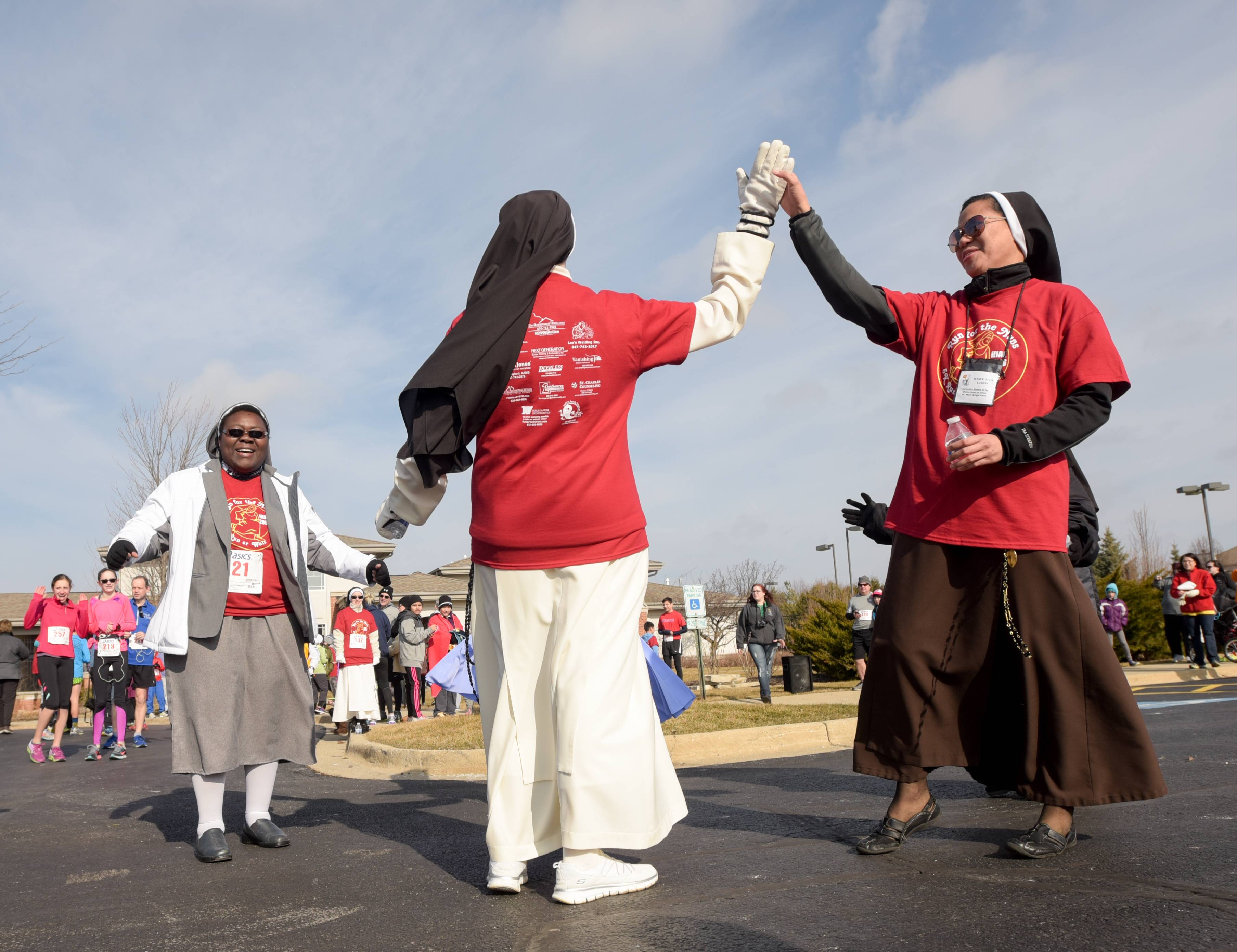 Sister Joachima high-fives Sister Mary Brigid Poso before the start of the Run for the Nuns 5K on Sunday in the Thornwood neighborhood of South Elgin.