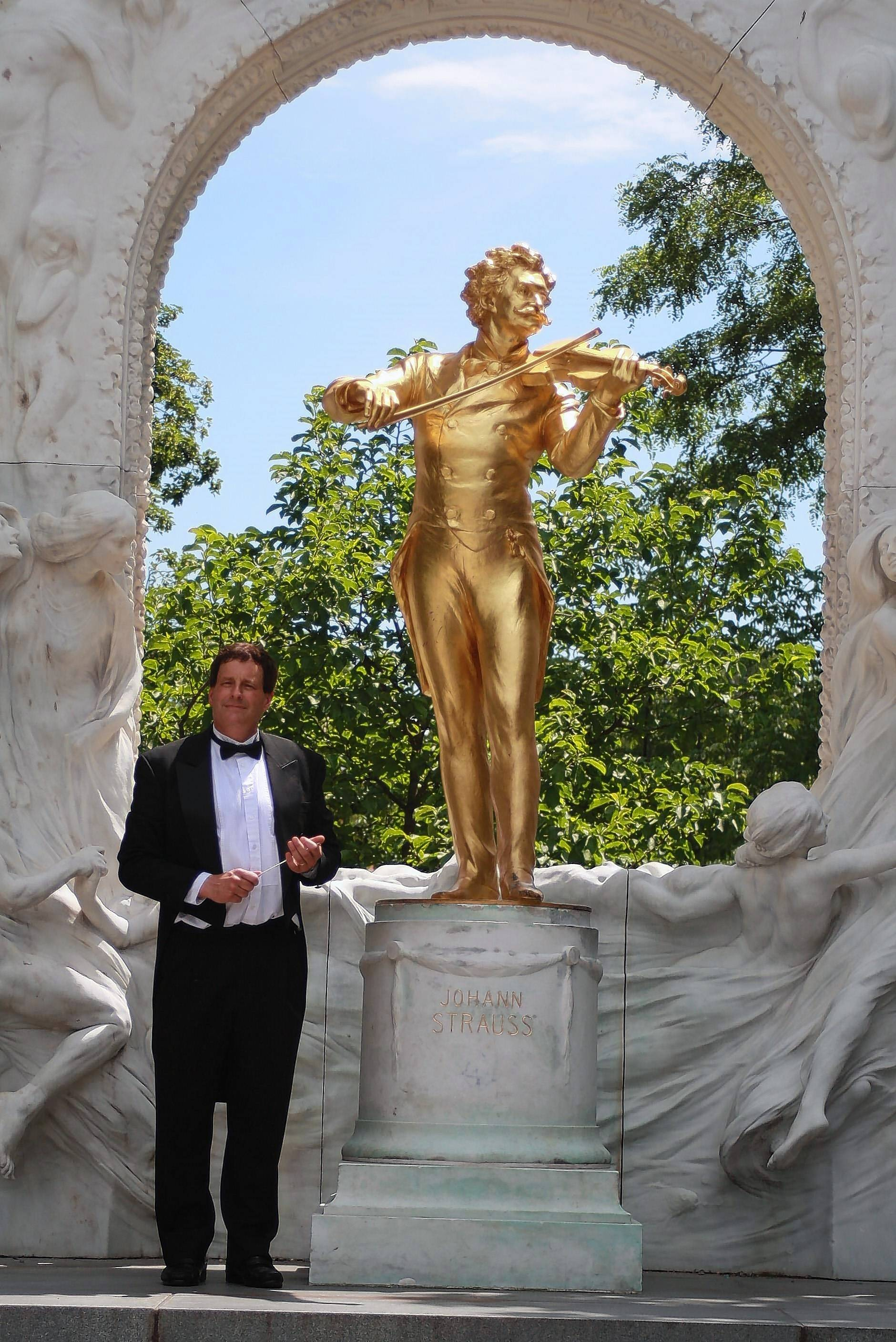 Ed Jacobi led the Buffalo Grove High School band on its first European concert tour in 1987 and will lead the band on one more tour, his 11th, in June. He is with a statue of Johann Strauss in Vienna's Stadtpark following the band's performance there in 2013.