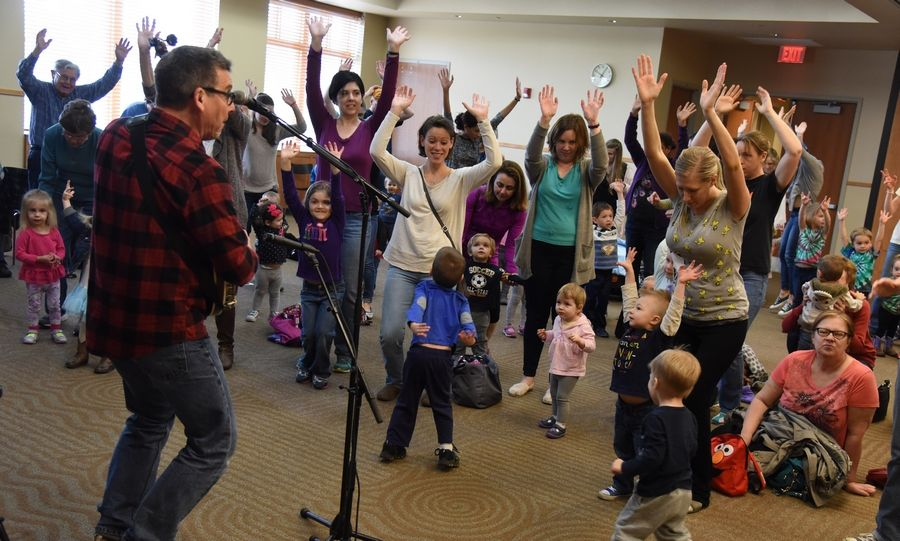 Children's entertainer Jim Gill has about 100 children, parents and caregivers up and moving during his family concert Wednesday at the Ela Area Public Library in Lake Zurich.