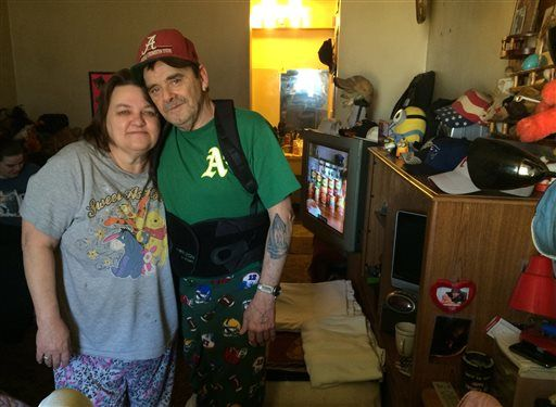 In this Jan. 29, 2016 photo, Steven Gibbs, stands with his wife, Debbie, in the motel room they share with their daughter and son-in-law in Murfreesboro, Tenn. Gibbs, whose disability check and wife's wages don't leave enough for an apartment security deposit, says he could never satisfy a probation officer who wanted $45 every week for company fees and court fines.