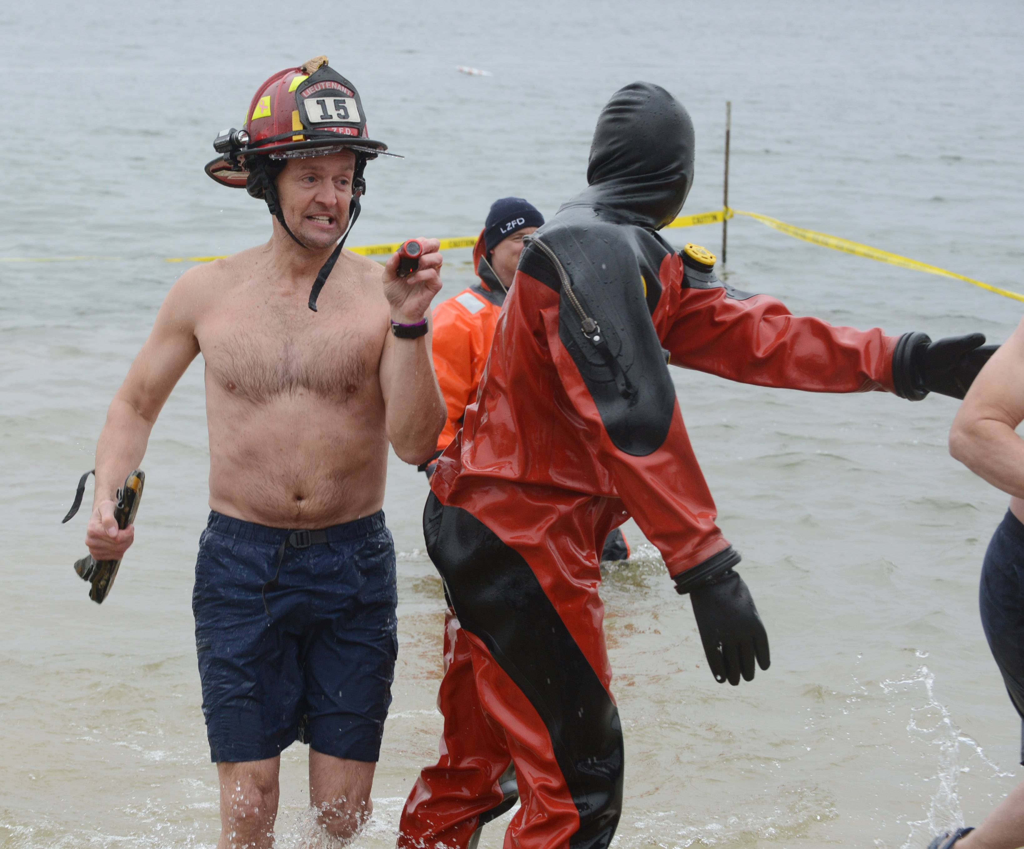 Lake Zurich Fire Rescue Deputy Chief Rick Johnson exits the frigid lake water during the Purple Polar Plunge at Breezewald Park and Beach in Lake Zurich Saturday.