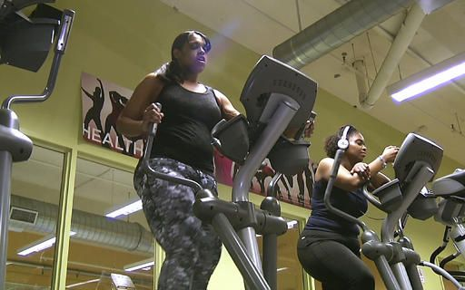 Monisha Long, left, works on a elliptical machine in Boston's Dorchester neighborhood. Doctors treating chronic health problems increasingly are prescribing exercise instead of medicines for their patients.