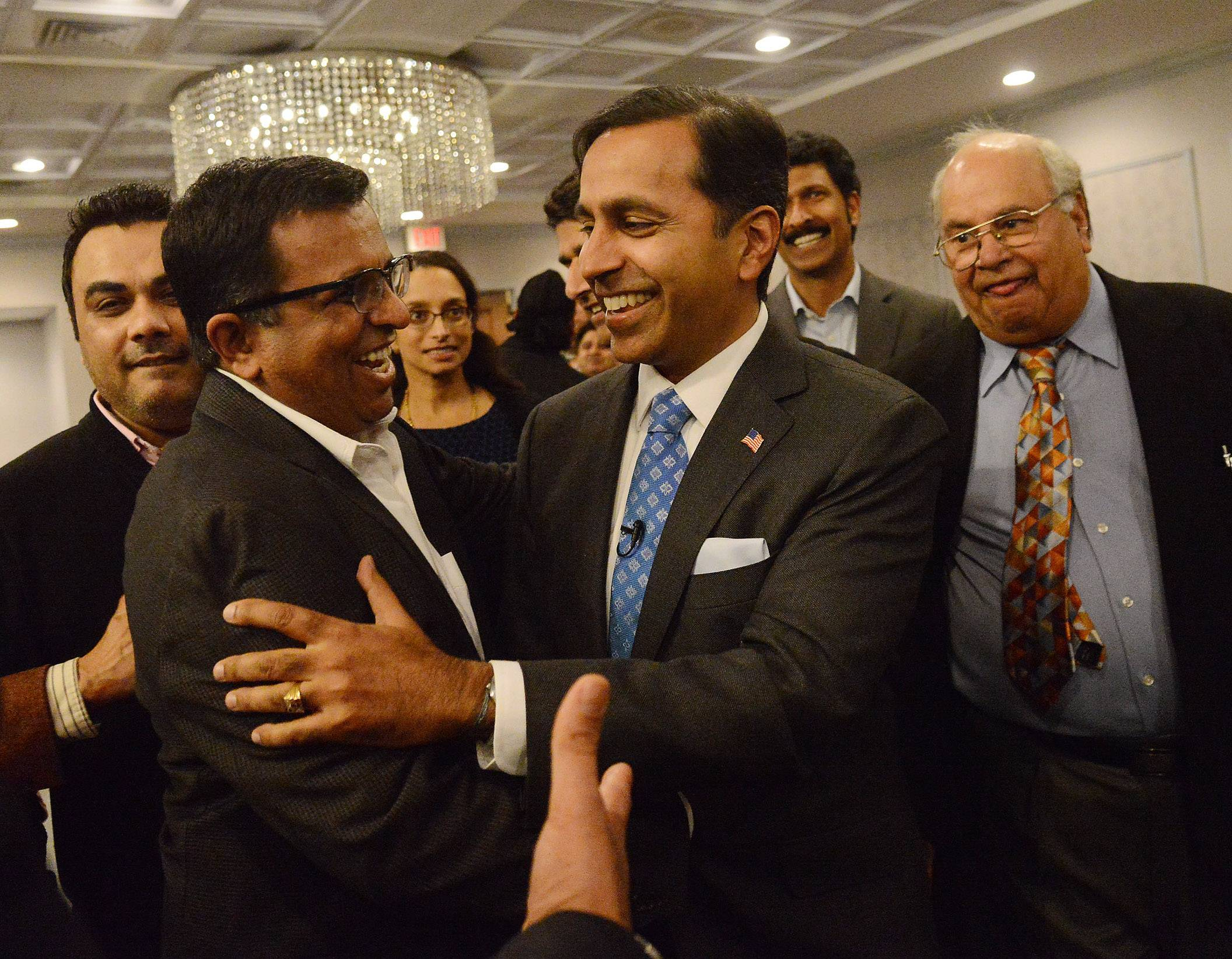 Raja Krishnamoorthi, right, Democratic candidate for the 8th Congressional District, is congratulated by supporters on his way to the podium for his victory speech Tuesday. Krishnamoorthi's victory in Tuesday's Democratic primary could portend a growing influence of Indian-Americans on the suburban political scene, he and others say.