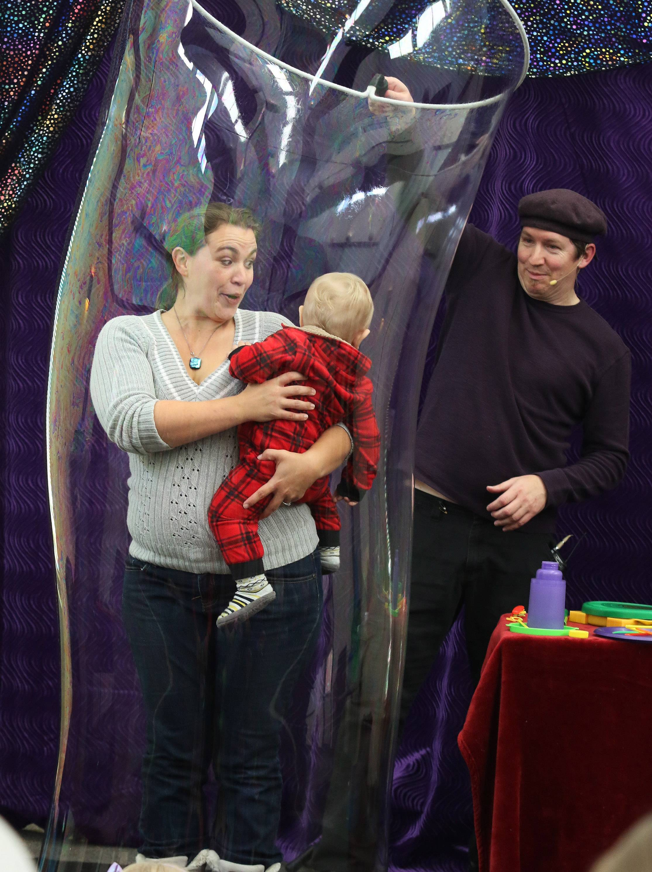 "Bubbleologist Geoff Akins captures Lindenhurst resident Jennifer Flatley and her one-year-old son, Declan, in a bubble during ""Bubble Wonders"" at the Lake Villa Public Library. Hannah created a bubble volcano, a bubble merry-go-round, and captured a children in a bubble at the show."