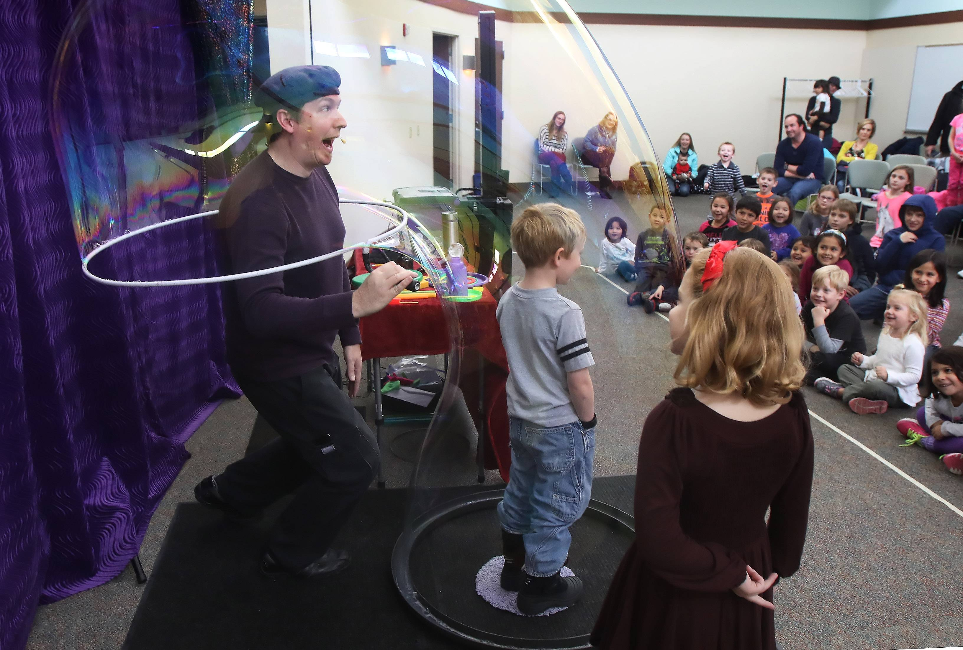 "Bubbleologist Geoff Akins-Hannah captures himself and Hans Larson, 5, into the same bubble during ""Bubble Wonders"" at the Lake Villa Public Library. Akins created a bubble volcano, a bubble merry-go-round, and captured a kid in a bubble at the show."