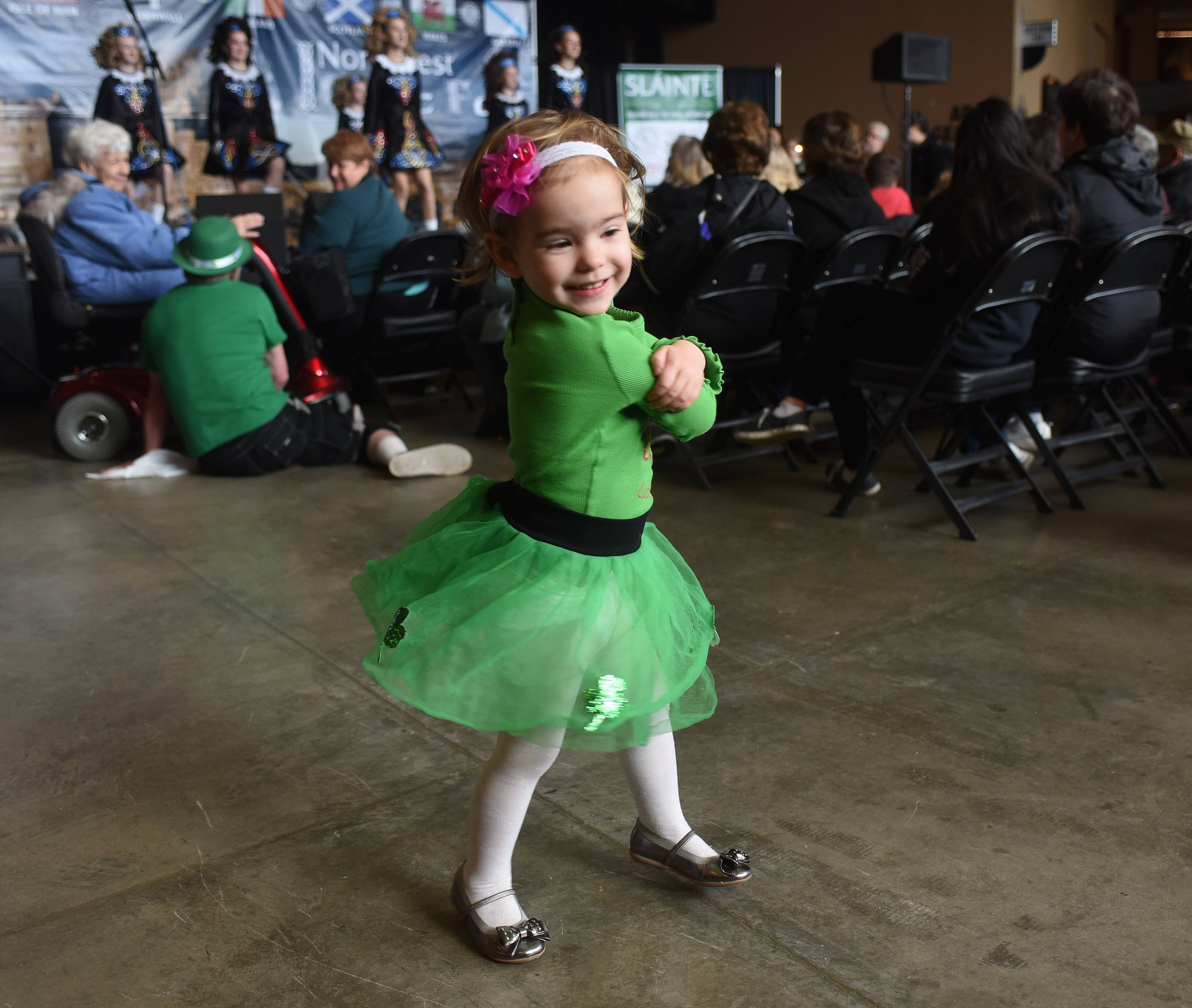Audience member Peyton Hoffman, 2, of Hoffman Estates dances while the Rebecca McCarthy School of Irish Dance performs on stage during the fifth annual Northwest Celtic Fest at the Sears Centre in Hoffman Estates Saturday. Hoffman was attending the event with her twin brother, Jadon, and her mom, Julie.
