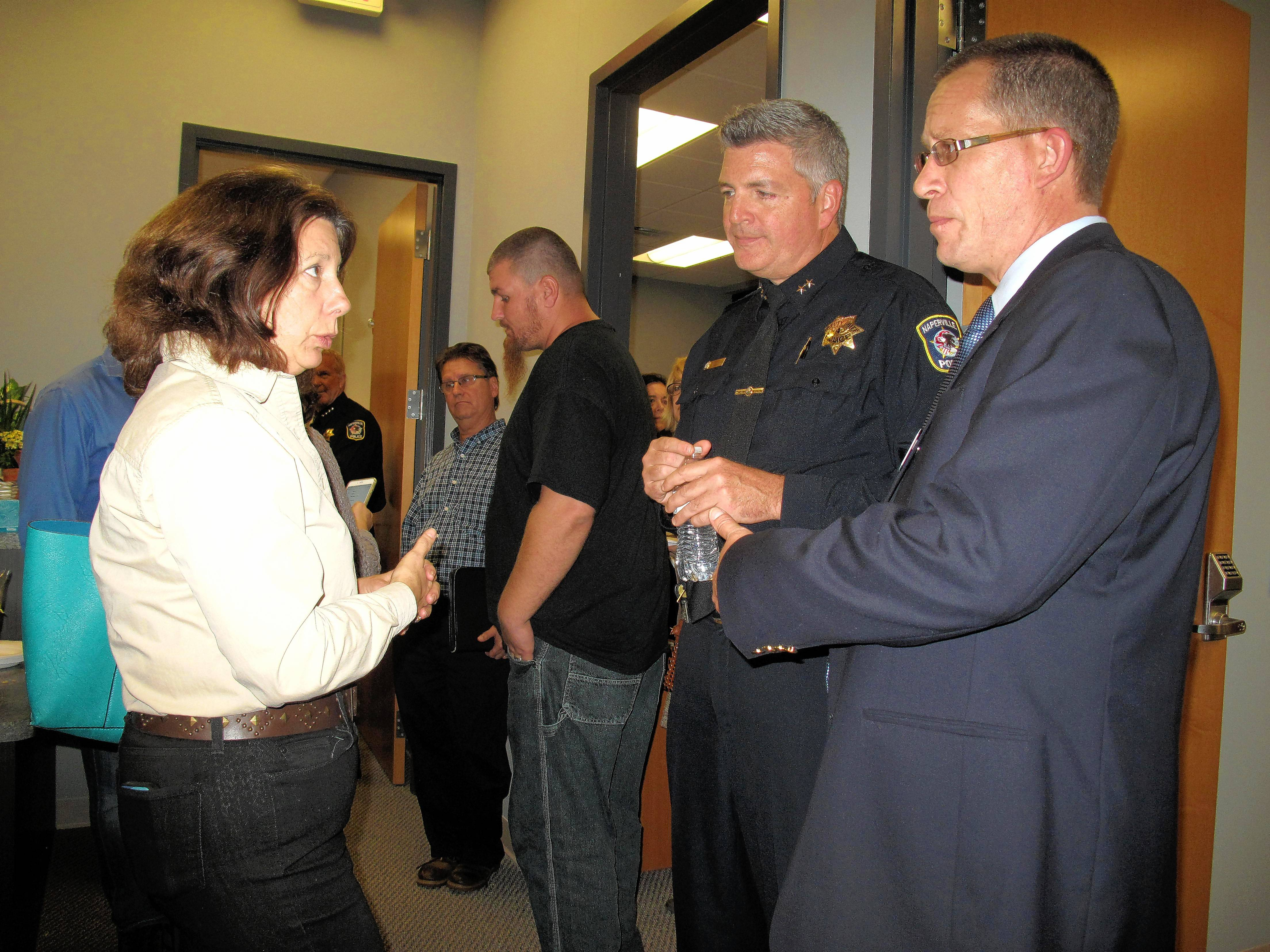 Naperville Deputy Police Chief Brian Cunningham, center, is leading creation of a program called Connect for Life, which launches Monday, to help heroin users find appropriate treatment. Banyan Treatment Center in downtown Naperville, where Cunningham talks with Caroline Kacena, who lost her son to an overdose, and Tim Ryan, who runs A Man In Recovery Foundation, is one of several participating treatment facilities.