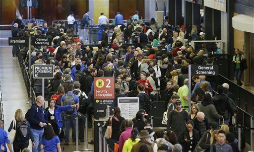 In this March 17, 2016, photo, travelers wait in line for security screening at Seattle-Tacoma International Airport in Seattle. Fliers will likely face massive security lines at airports across the country this summer, with airlines already warning passengers to arrive at least two hours early or risk missing their flight.