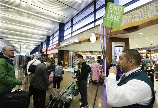 "ADVANCE FOR RELEASE WEDNESDAY, MARCH 30, AND THEREAFTER - In this March 17, 2016, photo, Jeff Molina, a ""pathfinder"" worker at Seattle-Tacoma International Airport in Seattle uses a two-way radio to get information about crowd levels at other security checkpoints as he holds a sign marking the end of an hour-long line for security screening that stretched past several concourse businesses."