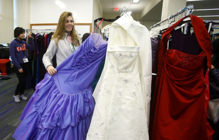 "Sarah Bentson of Waubonsie Valley High School looks over dresses during the ""Say Yes to the Prom Dress"" program Saturday at the Aurora Santori Public Library. Several librarians collected more than 300 gently-used dresses to be given away in exchange for a food donation."