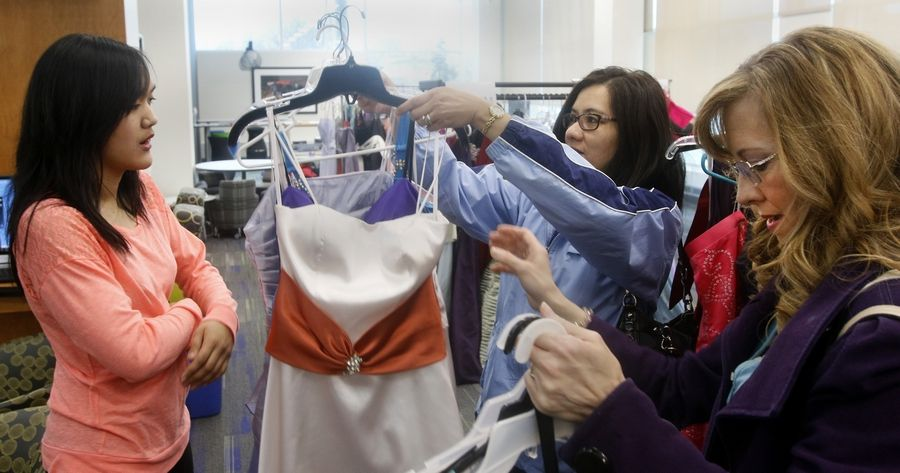 "Bea Mangayaay, left, of Oswego High School looks over dresses during the ""Say Yes to the Prom Dress"" program Saturday at the Aurora Santori Public Library. Above, Mangayaay gets help from her mother Jenny Mangayaay, center, and family friend Nancy Scheri, right, in selecting her dress."