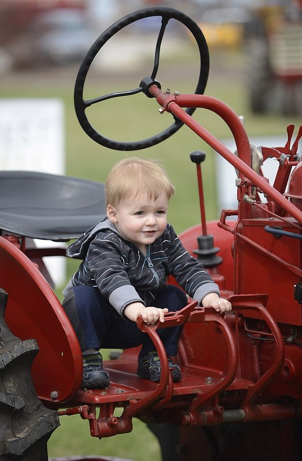 Liam Becker, 1½, of Wheaton, works the pedals with his hands at last year's Kane County Farm Bureau Touch-A-Tractor event in St. Charles.