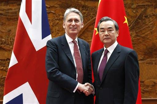 British Foreign Secretary Philip Hammond, left, poses with Chinese Foreign Minister Wang Yi for photographers prior to a meeting in Beijing Saturday, April 9, 2016. (Kim Kyung-Hoon/Pool Photo via AP)
