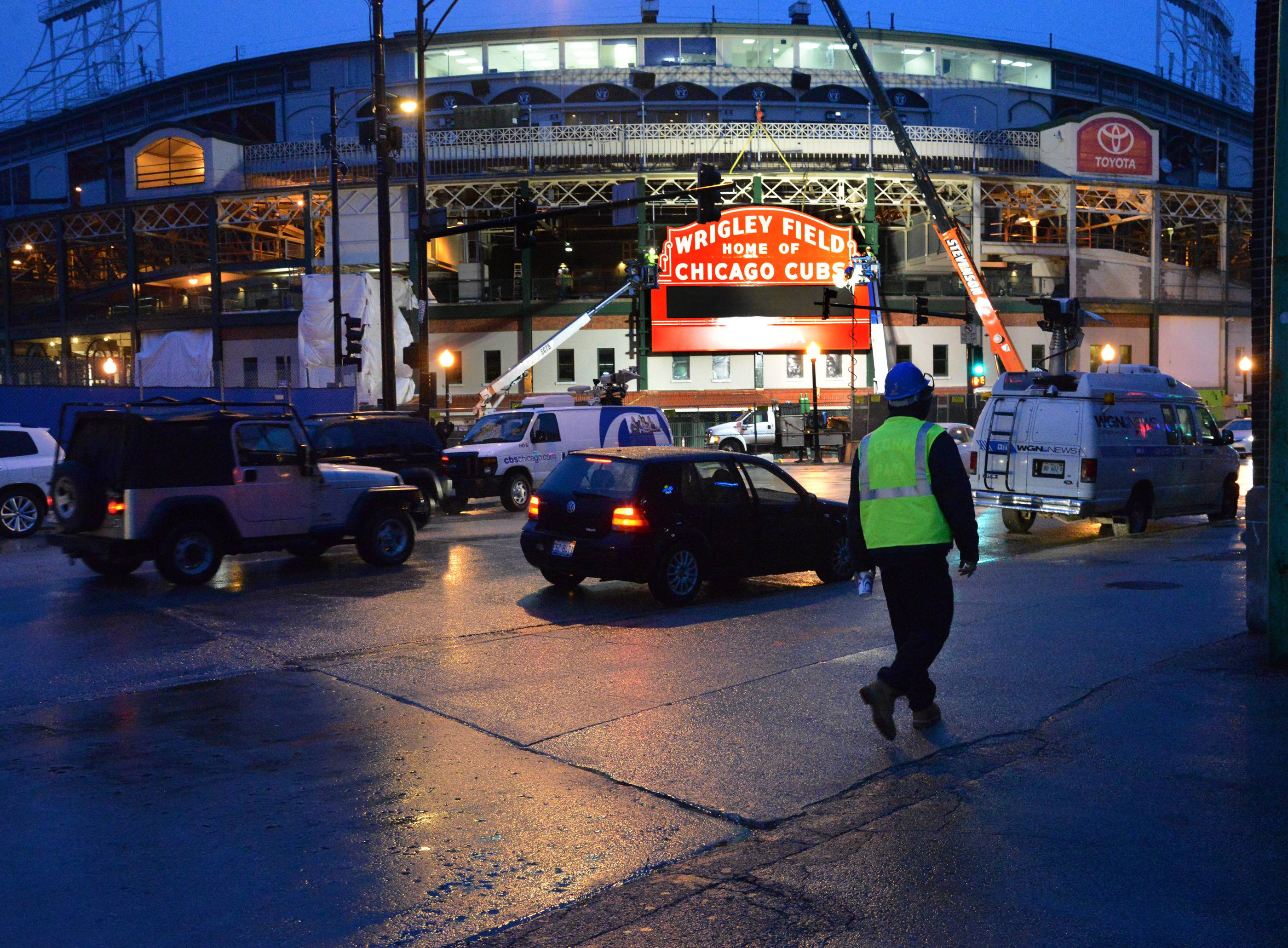 A construction worker walks on Addison Street after crews work for hours in the rain to reinstall the historic Wrigley Field Marquee Wednesday at Clark and Addison in Chicago.