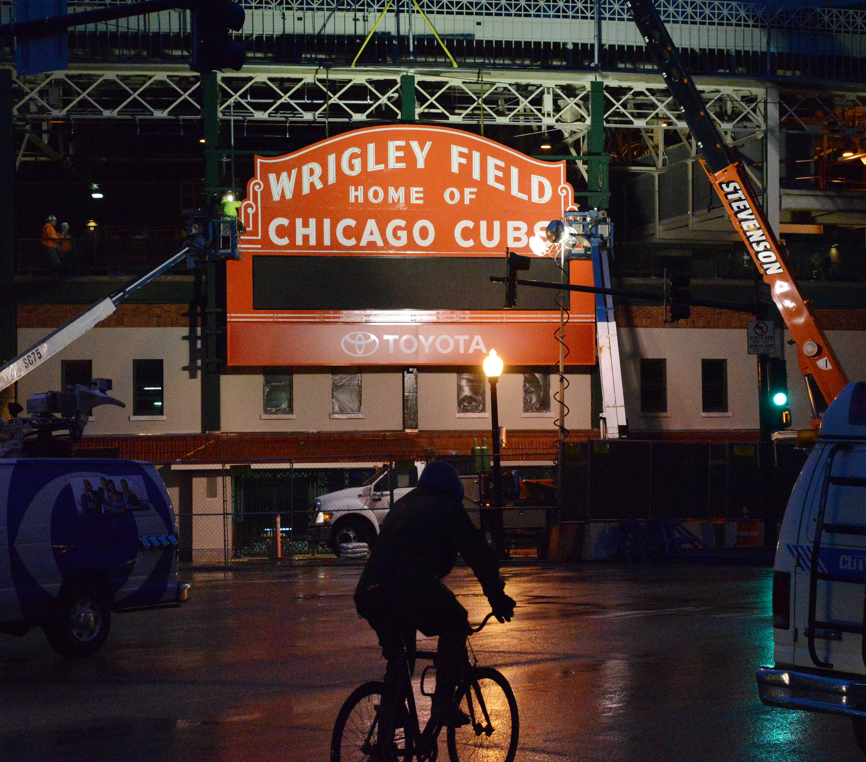 A bicyclist pedals past after crews work for hours in the rain to reinstall the historic Wrigley Field Marquee Wednesday at Clark and Addison in Chicago after is was restored.
