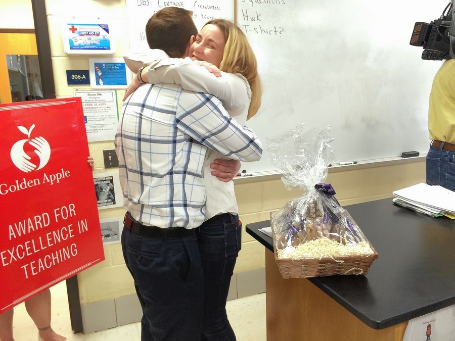 Jeff Grant, an AP biology and anatomy and physiology teacher, hugs his wife, Gretchen, after he learned he won a Golden Apple Award for Excellence in Teaching.