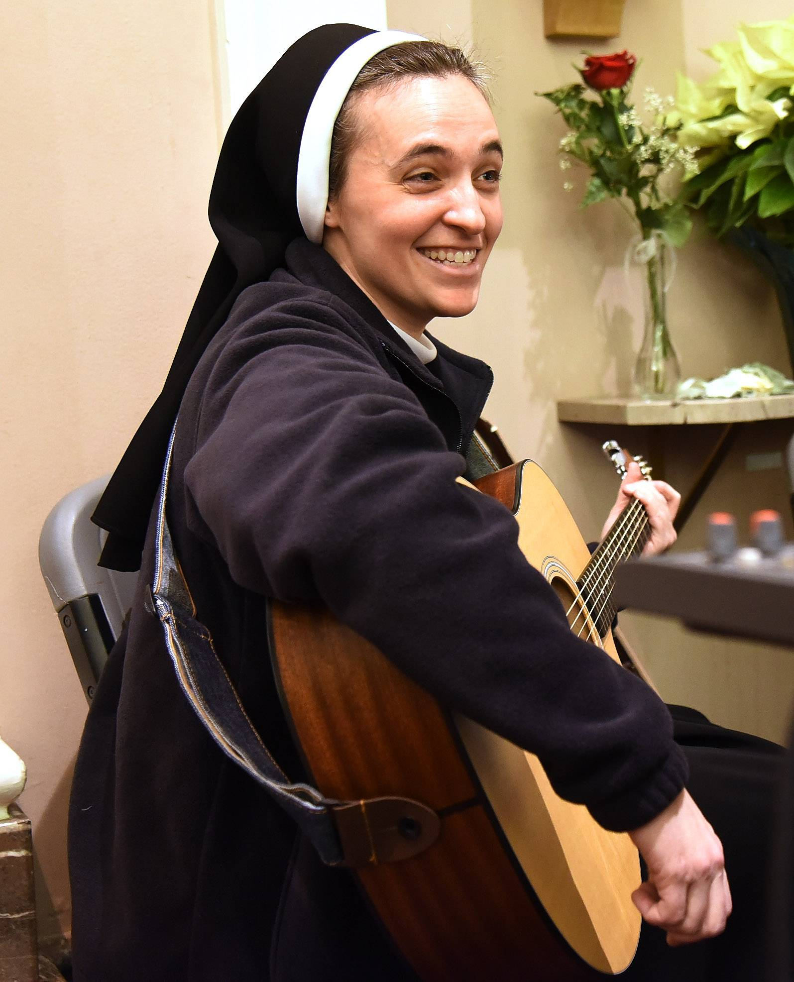 Sister Faustina Ferko plays guitar with the youth choir during a Sunday evening mass at St. James Parish in Arlington Heights.